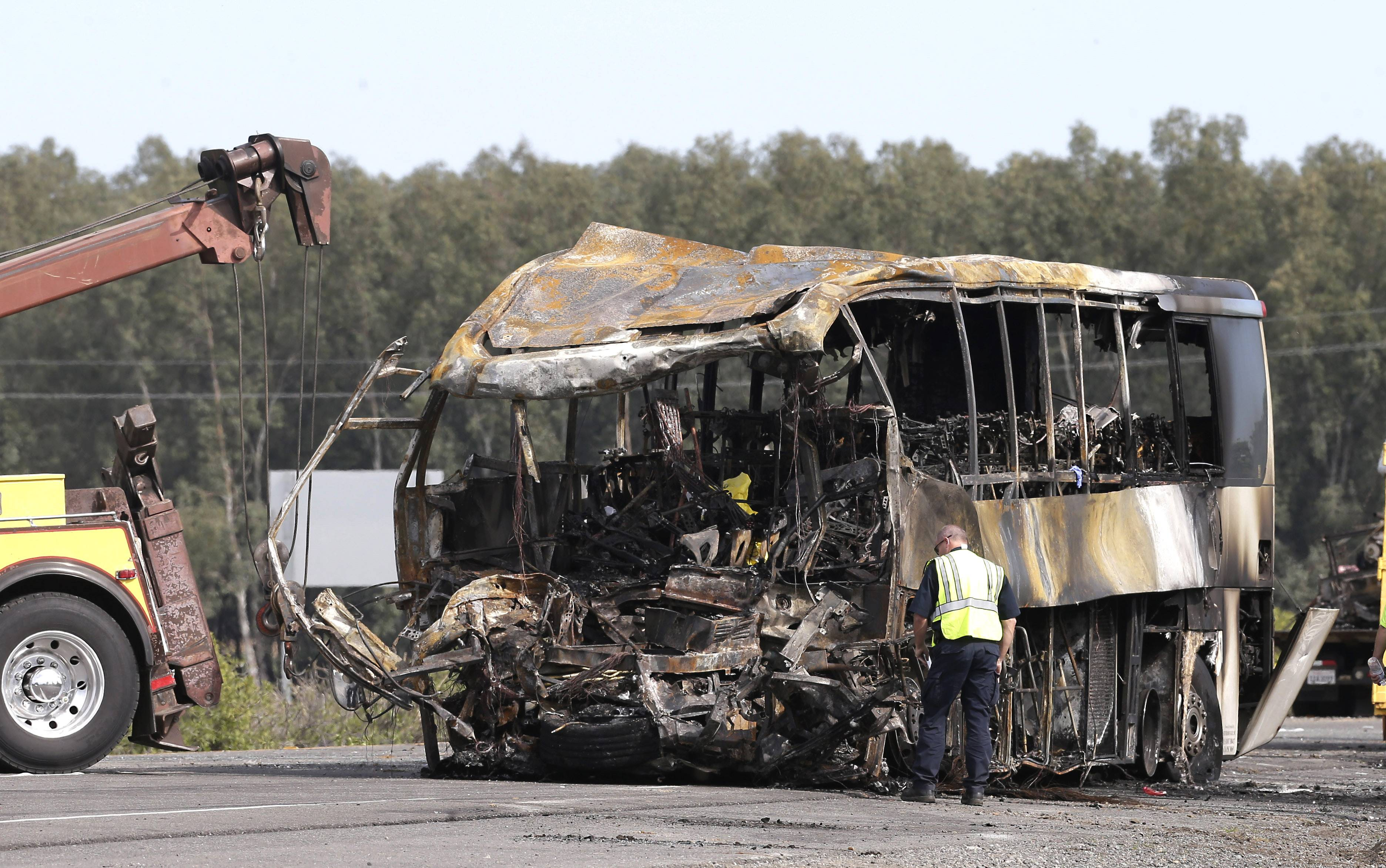 A California Highway Patrol Officer looks over the burned out remains of a tour bus, Friday, April 11, 2014, that collided with a FedEX truck on Interstate 5 Thursday in Orland, Calif.  At least ten people were killed and dozens injured in the fiery crash, Thursday, between the truck and a bus carrying high school students on a visit to a Northern California College.