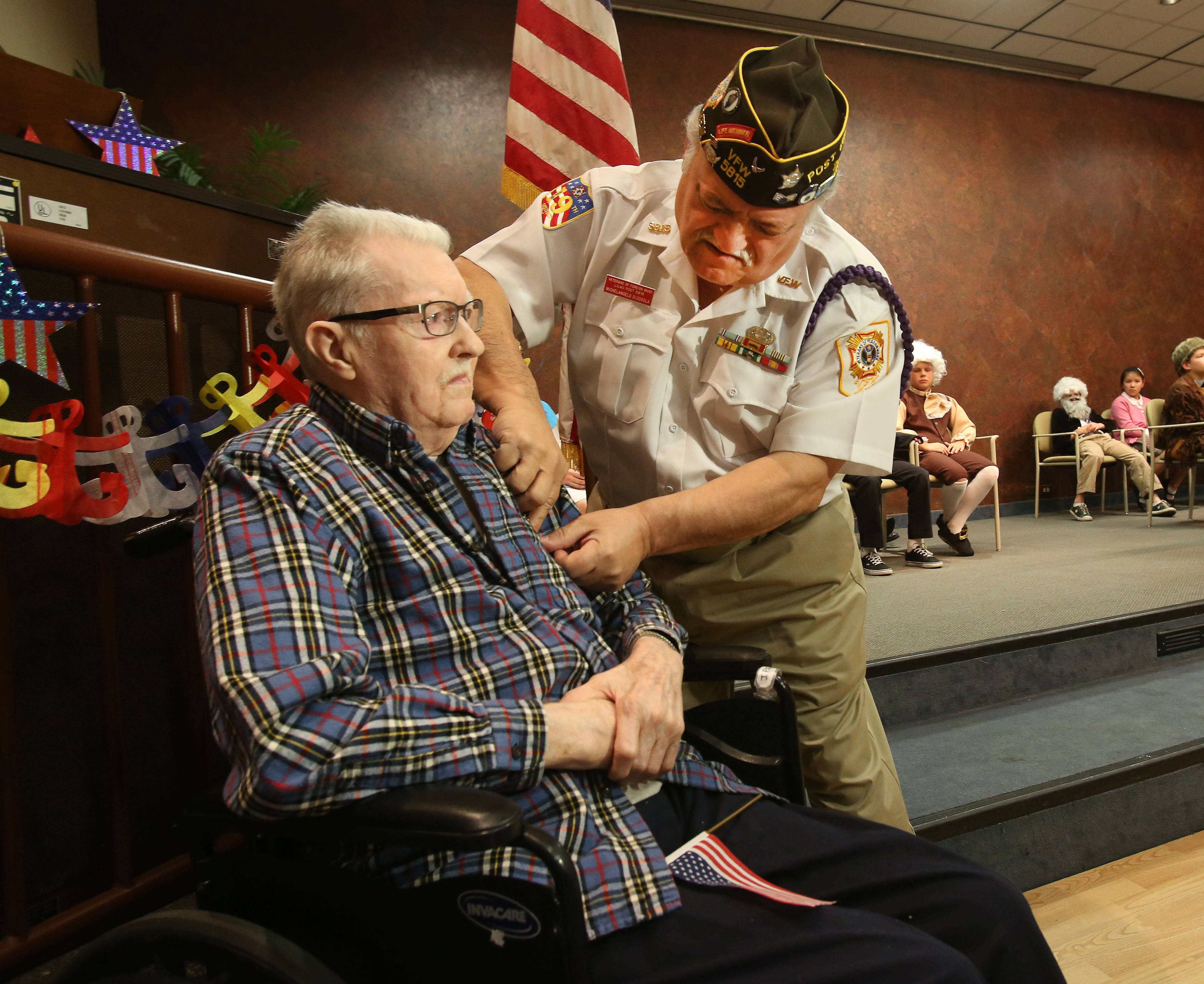 World War II veteran Jim Pfafflin receives medals recognizing his service in the U.S. Merchant Marine from VFW Post 5815 Commander Michelangelo Di Cosola. The medals were presented Friday during a ceremony at the Beacon Hill senior living community in Lombard.