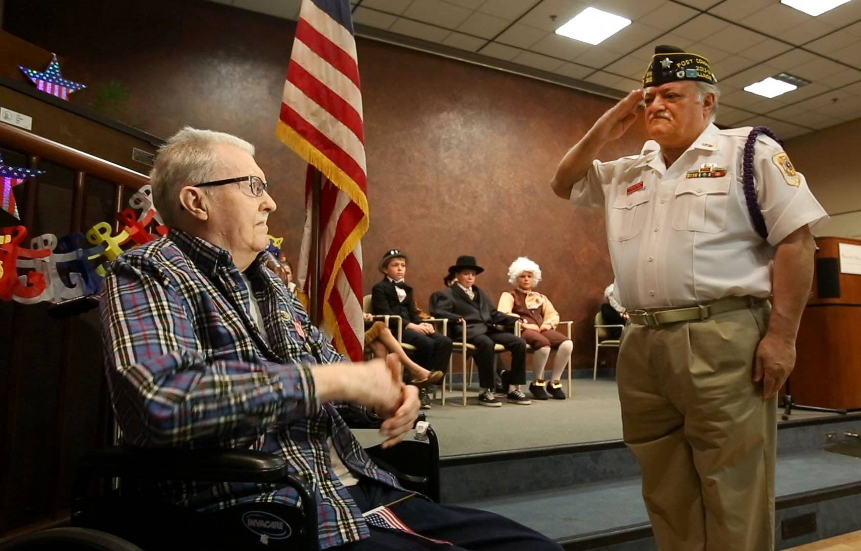 VFW Post 5815 Cmdr. Michelangelo Di Cosola, right, salutes World War II veteran Jim Pfafflin Friday in Lombard, shortly after he was presented with medals that recognized his service in the U.S. Merchant Marine more than 65 years ago.
