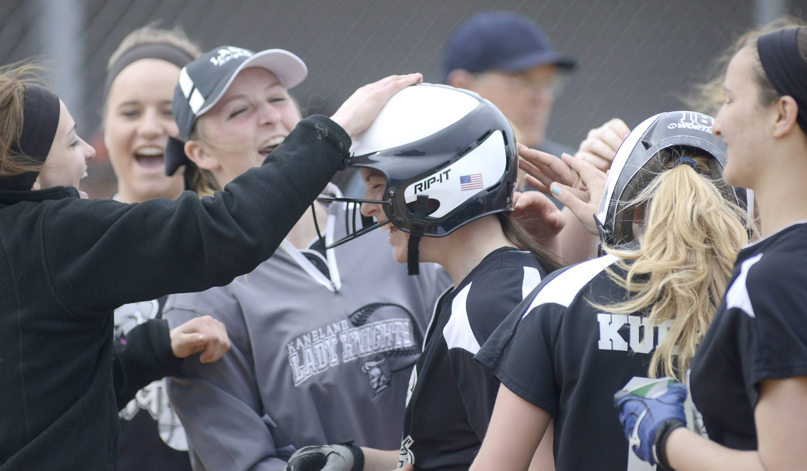 Kaneland's Morgan Weber, center, is congratulated at home plate after hitting a home run in the second inning against Batavia on Saturday.