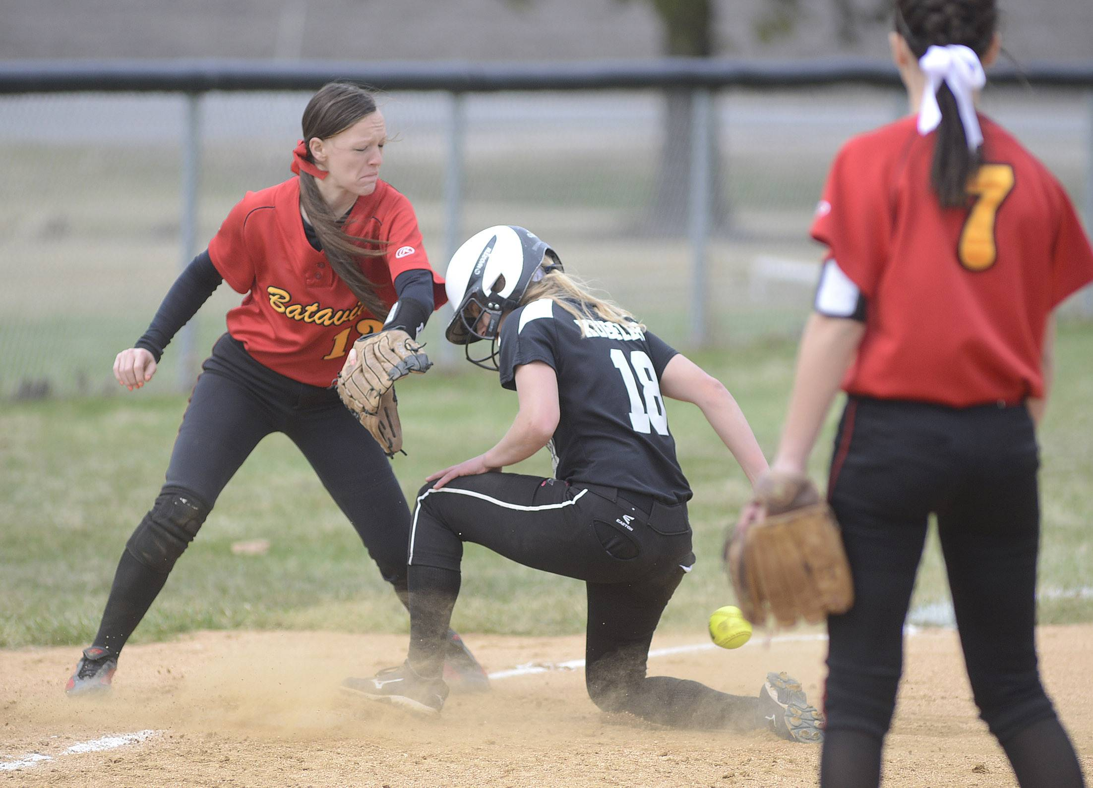 Kaneland's Paige Kuefler slides into third base, the ball bouncing off her as Batavia's Nina Karius reaches for the ball in the second inning on Saturday.