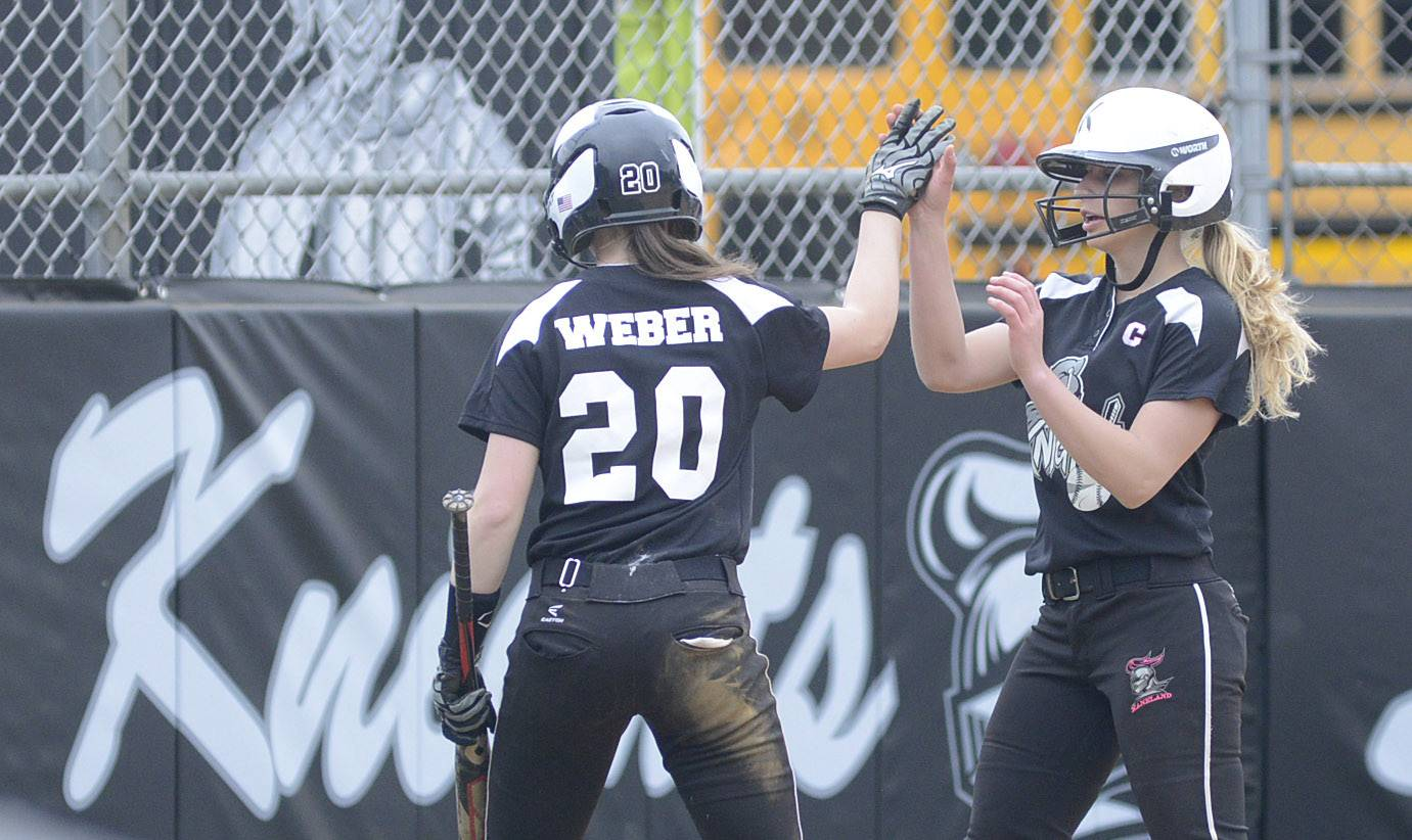 Kaneland's Morgan Weber (20) is congratulated by teammate Paige Kuefler after scoring in the first inning against Batavia on Saturday.