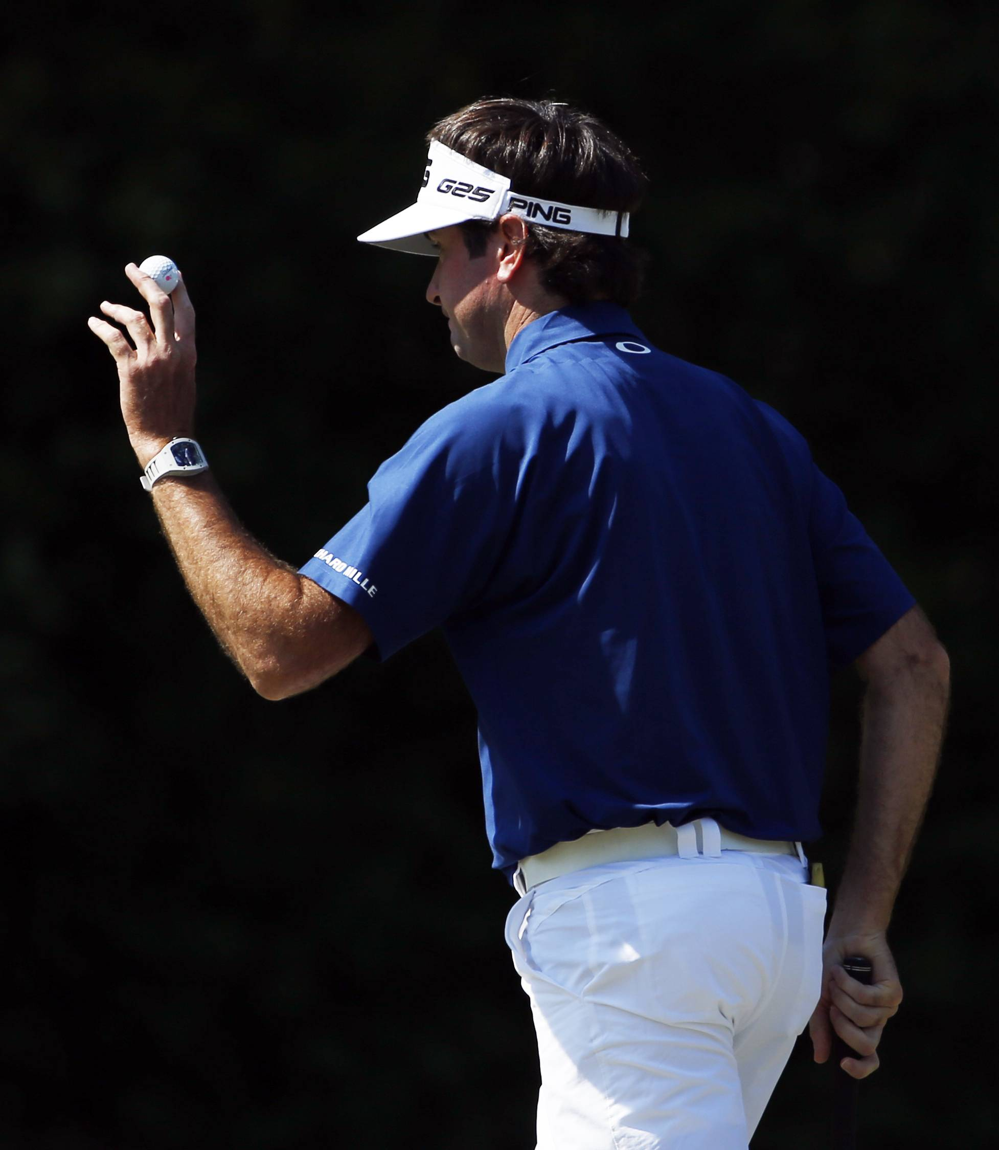 Bubba Watson holds up his ball after putting on the fourth hole during the third round of the Masters golf tournament Saturday in Augusta, Ga.
