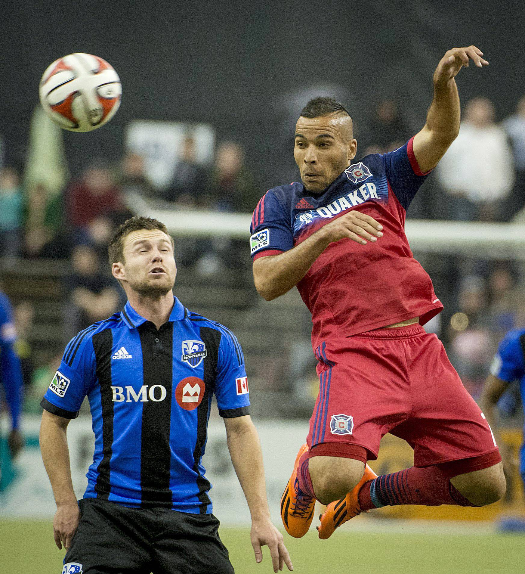 Montreal Impact's Jack McInerney stands near as the Chicago Fire's Alex heads the ball during a soccer game Saturday in Montreal.