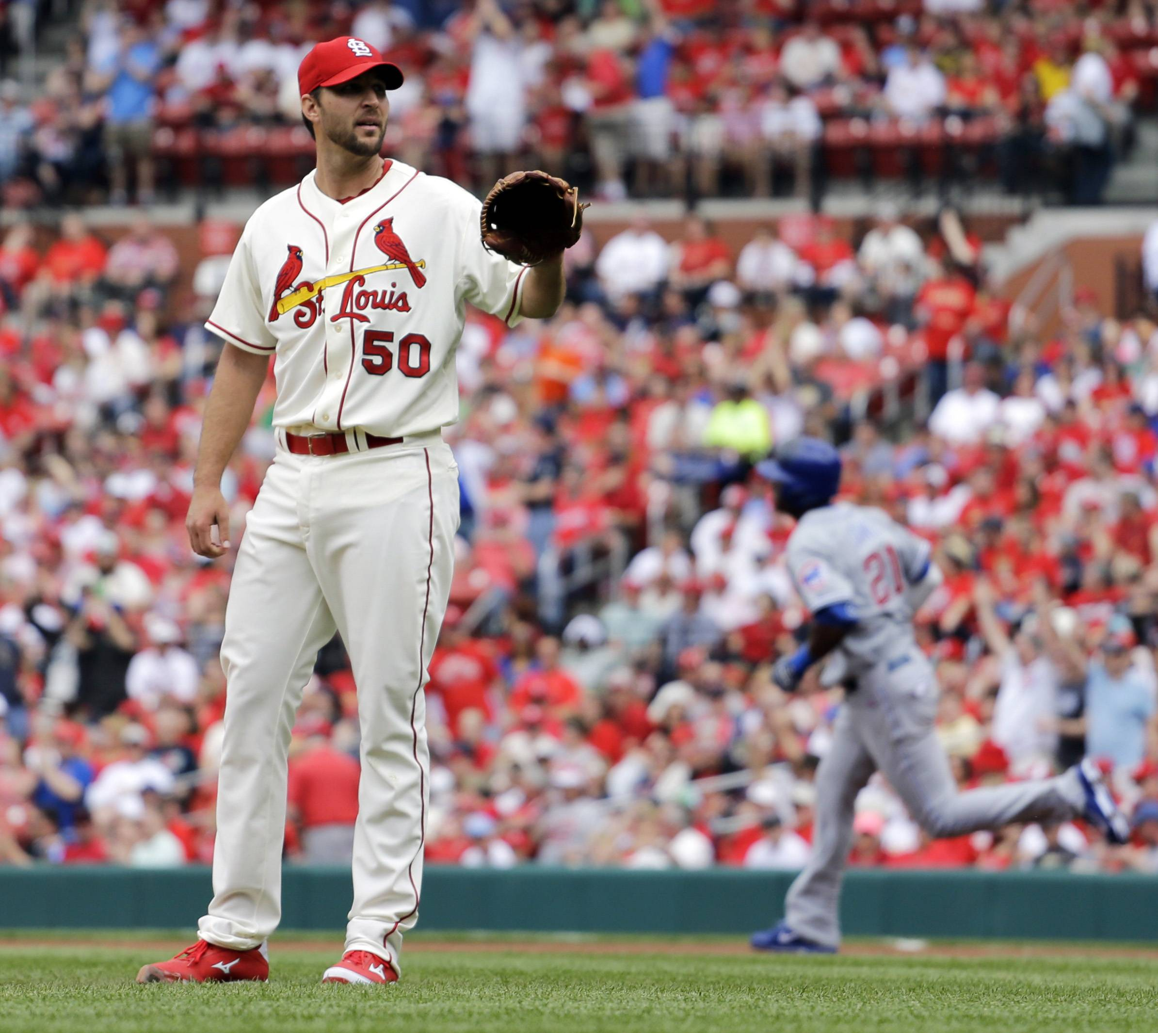 St. Louis Cardinals starting pitcher Adam Wainwright, left, waits for a new ball as Chicago Cubs' Junior Lake rounds the bases after hitting a solo home run during Saturday's game in St. Louis.
