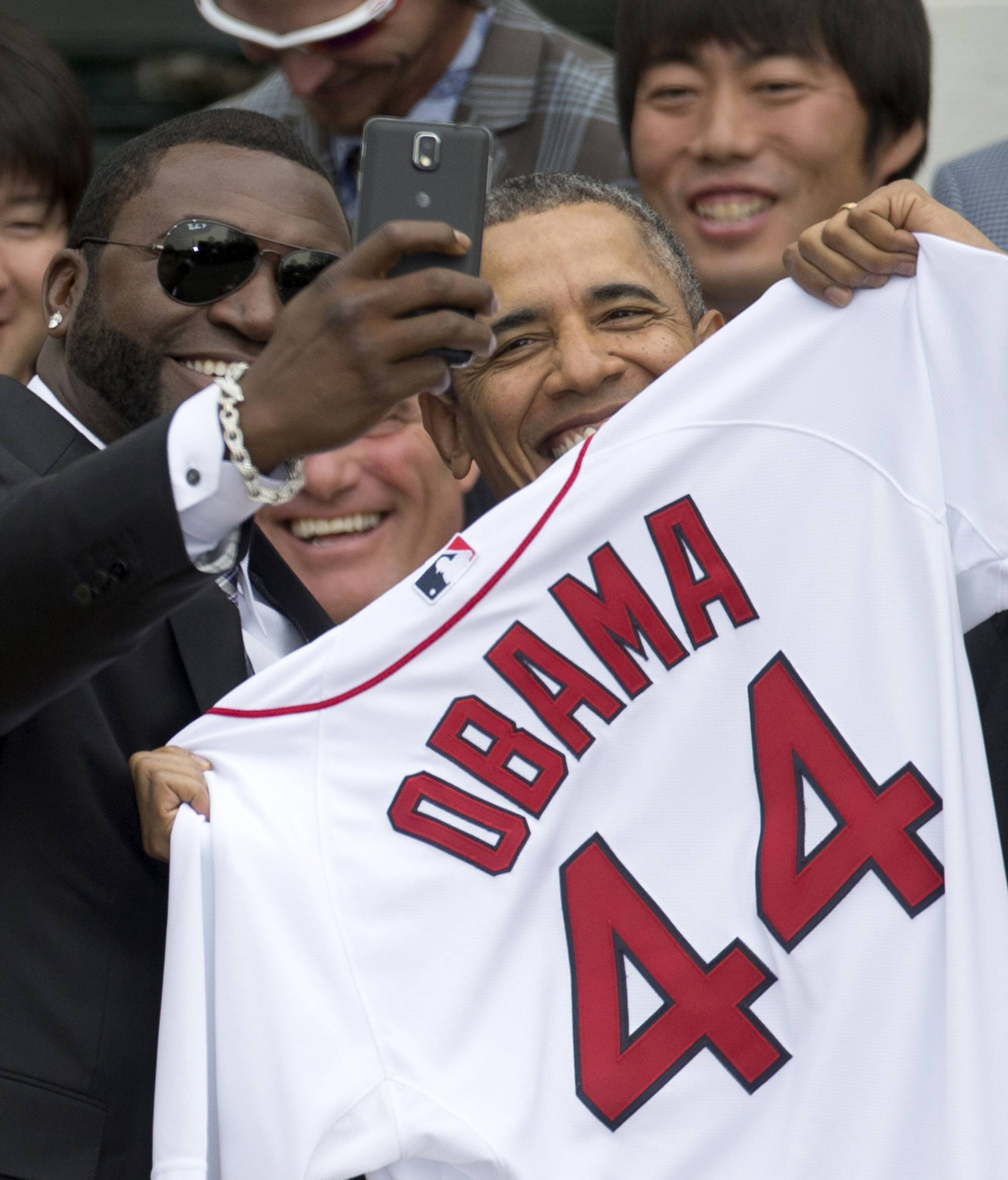 "Boston Red Sox designated hitter David ""Big Papi"" Ortiz takes a selfie with President Barack Obama, holding a Boston Red Sox jersey presented to him, during a ceremony on the South Lawn of the White House in Washington, where the president honored the 2013 World Series baseball champion Boston Red Sox."