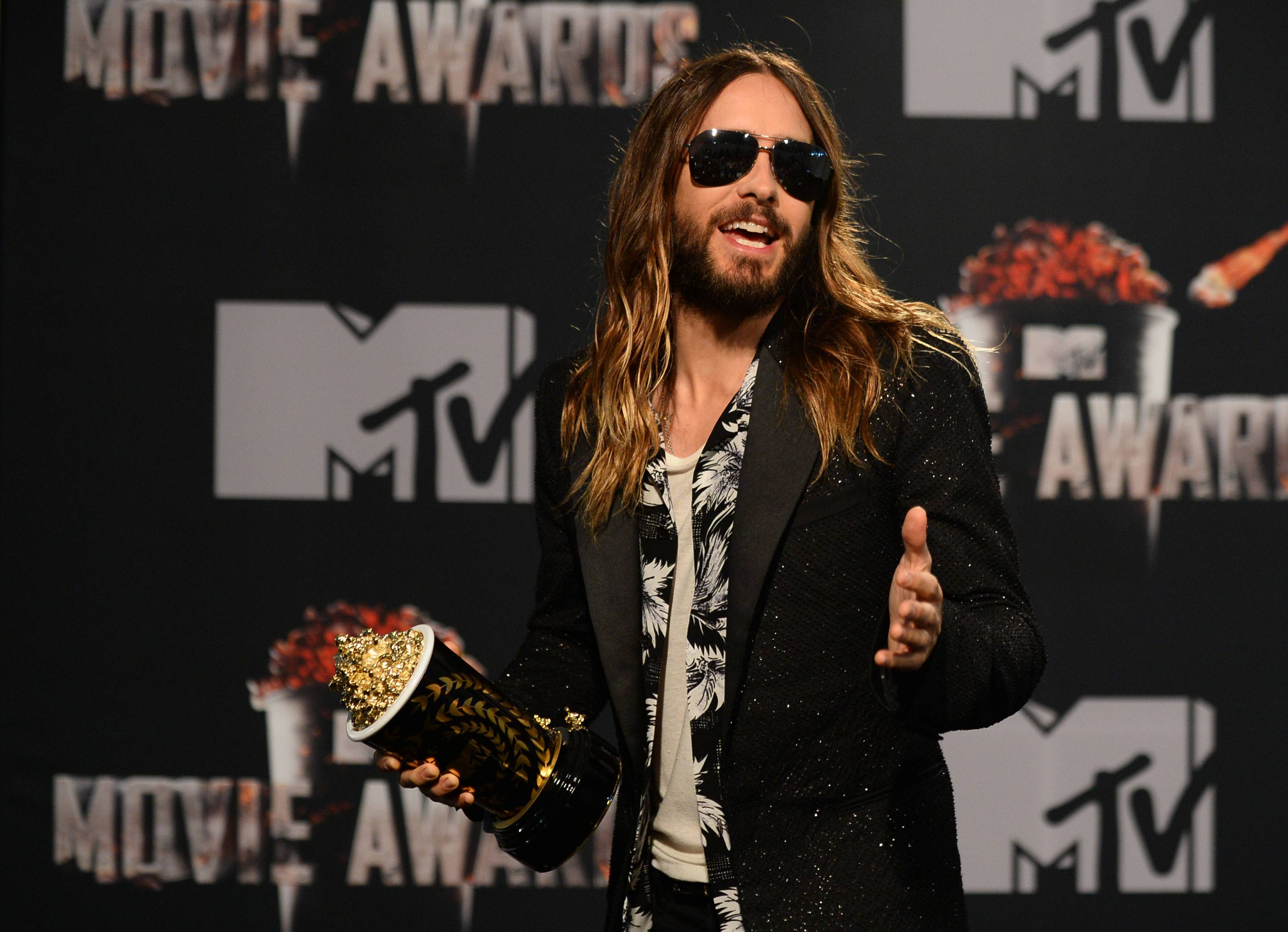"Jared Leto poses in the press room with the award for Best On-Screen Transformation for ""Dallas Buyers Club"" at the MTV Movie Awards on Sunday."