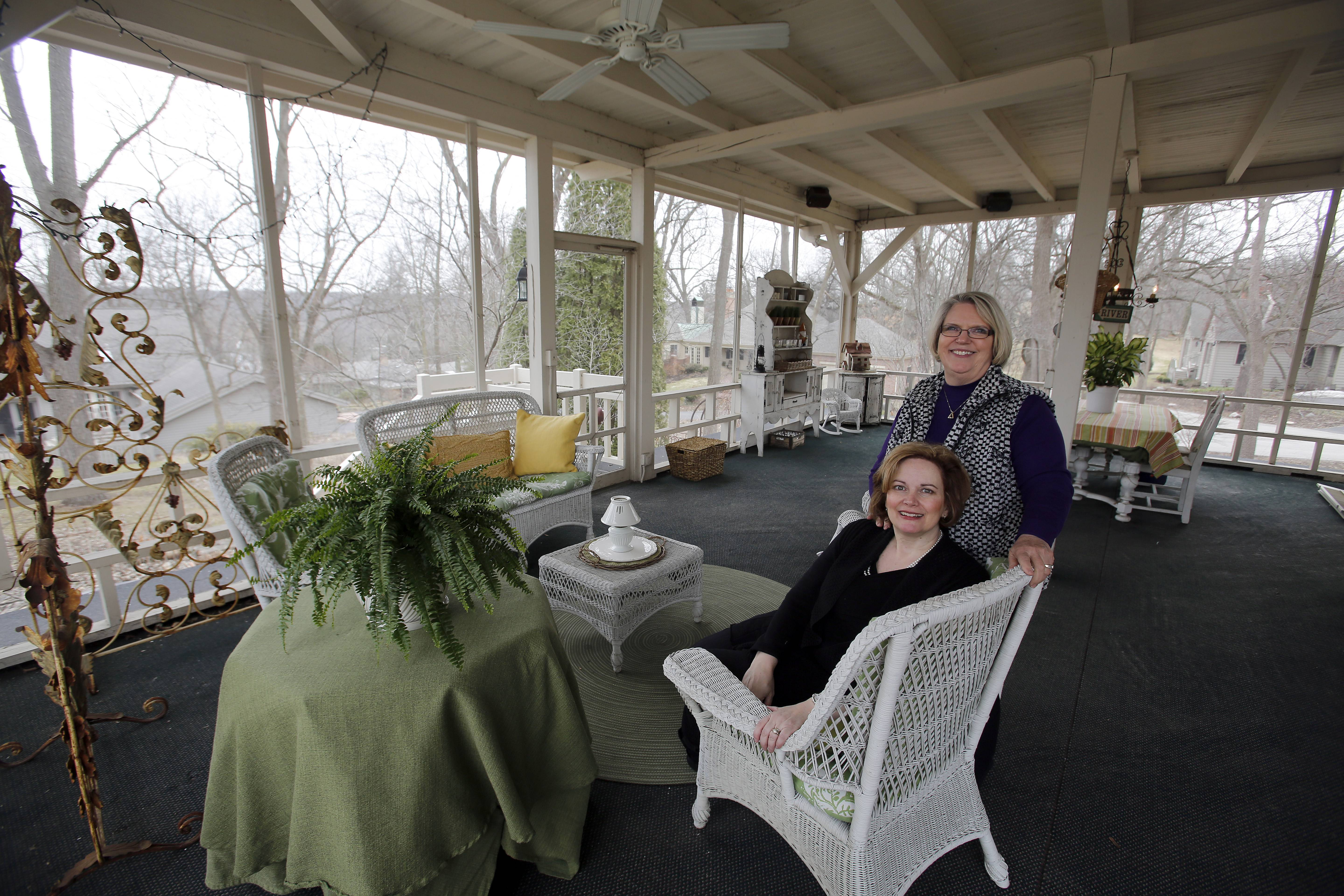 Homeowner Marsha Reinecke, sitting, and Realtor Patti Rambo show a massive rear porch the Reinecke family has enjoyed over the years.