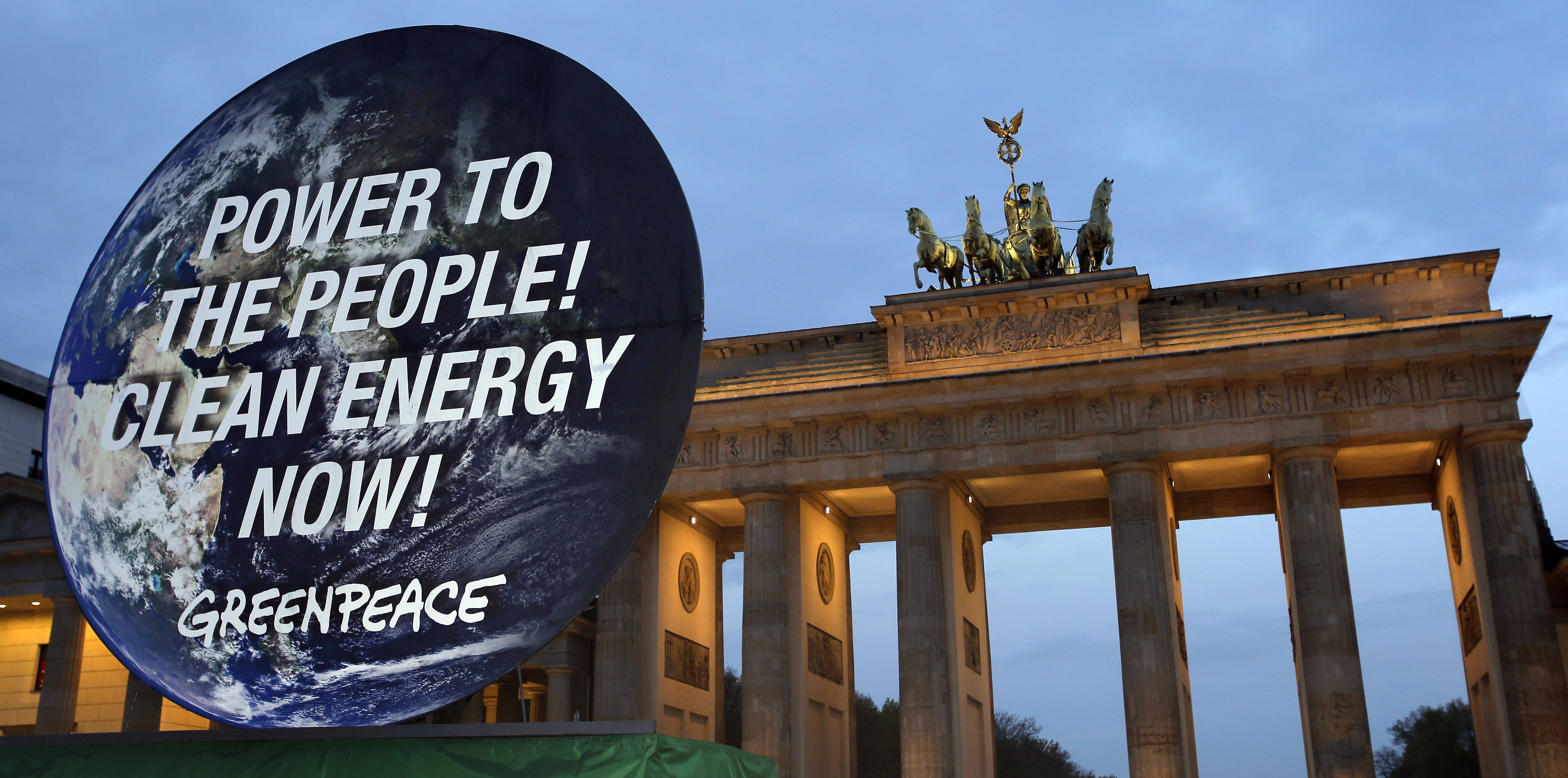 A giant poster of the international environmentalist organization Greenpeace is displayed in front of the Brandenburg Gate in Berlin, Germany, Sunday to support clean energy. After a one week meeting of the Intergovernmental Panel on Climate Change in Berlin the final document which is released on Sunday said a global shift to renewable energy from fossil fuels like oil and coal are required to avoid potentially devastating sea level rise, flooding, droughts and other impacts of warming.