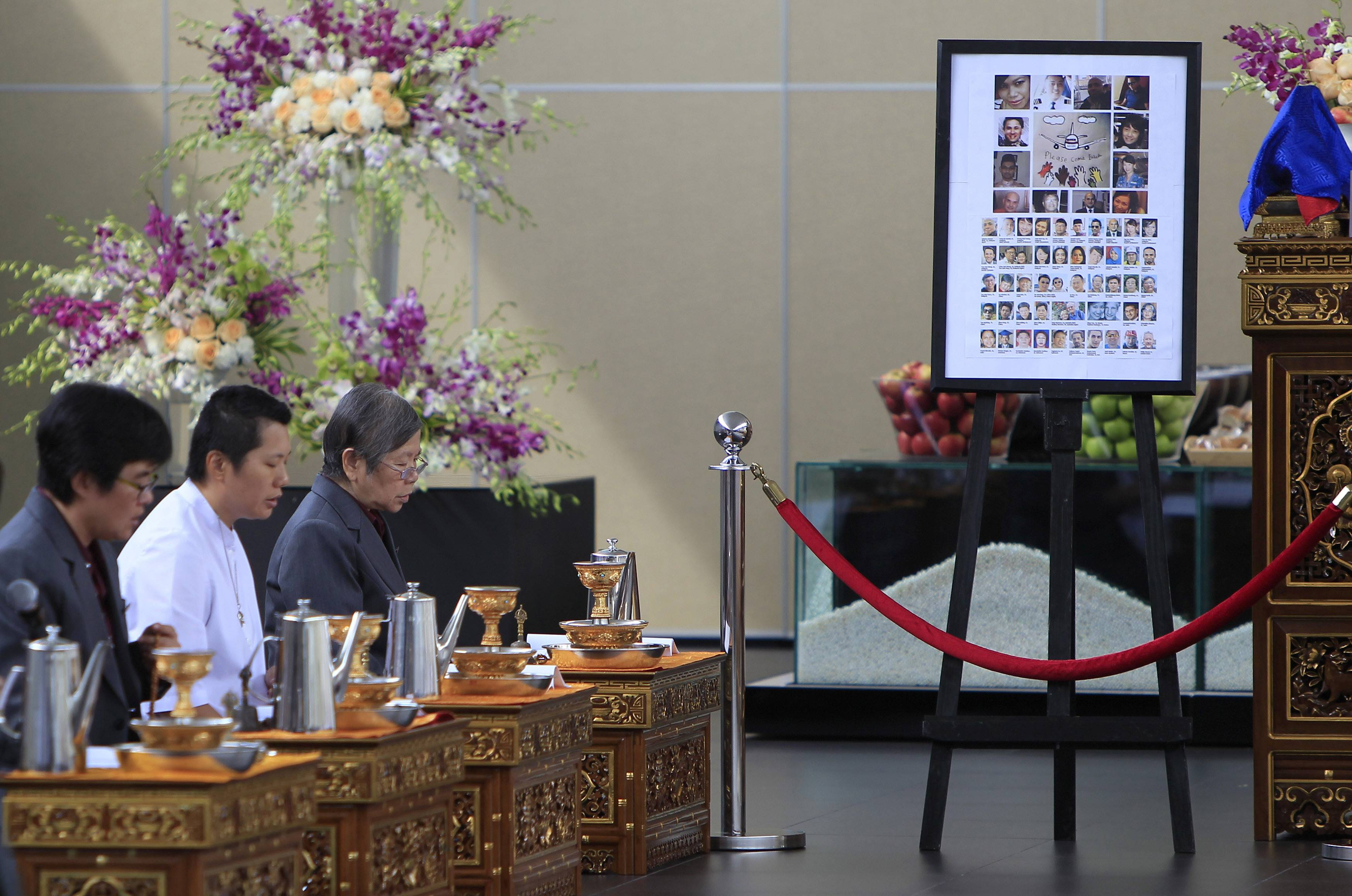 Photos of passengers and crew members onboard the missing Malaysia Airlines Flight 370 are placed at Kechara Forest Retreat as Buddhist pastors offer prayers for them in Bentong, outside Kuala Lumpur, Malaysia, Sunday.