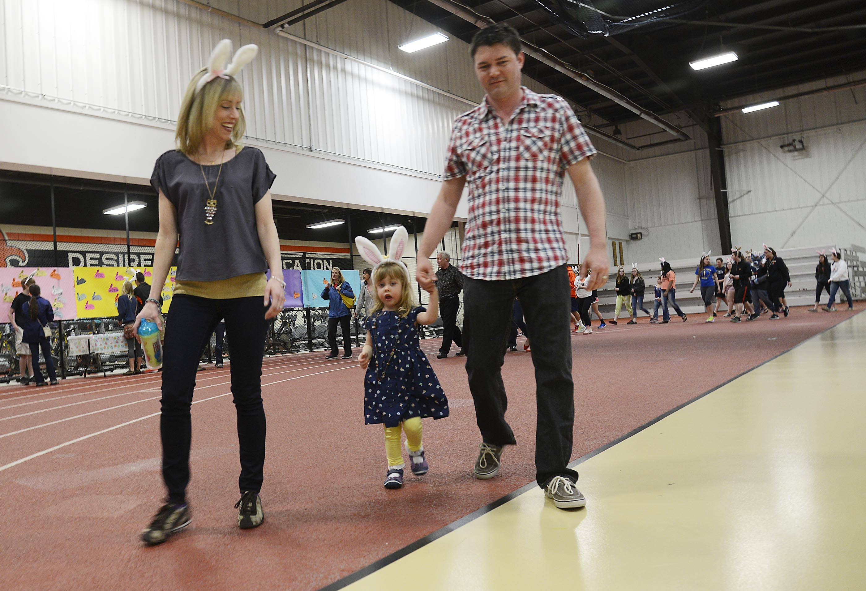 Caitlin Cox, almost 3, walks with her parents, Meghan and Jeff, during a Juvenile Arthritis benefit walk organized by the St. Charles East High School student council Sunday at the school's Sports Center. She was diagnosed with juvenile arthritis last September.