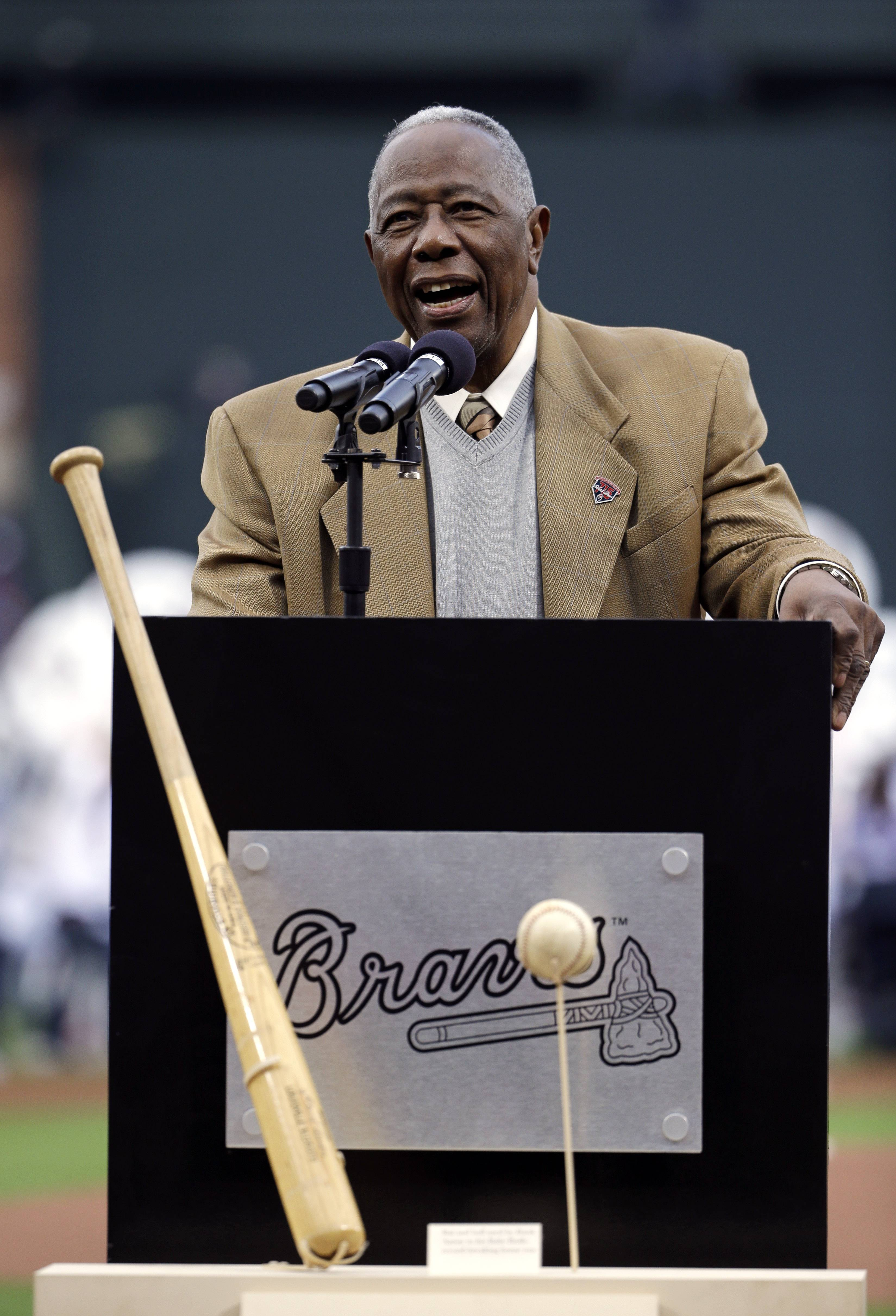 Hank Aaron speaks during a ceremony celebrating the 40th anniversary of his 715th home run as the actual bat and ball from the hit stand on display before the start of a baseball game between the Atlanta Braves and the New York Mets on April 8 in Atlanta.