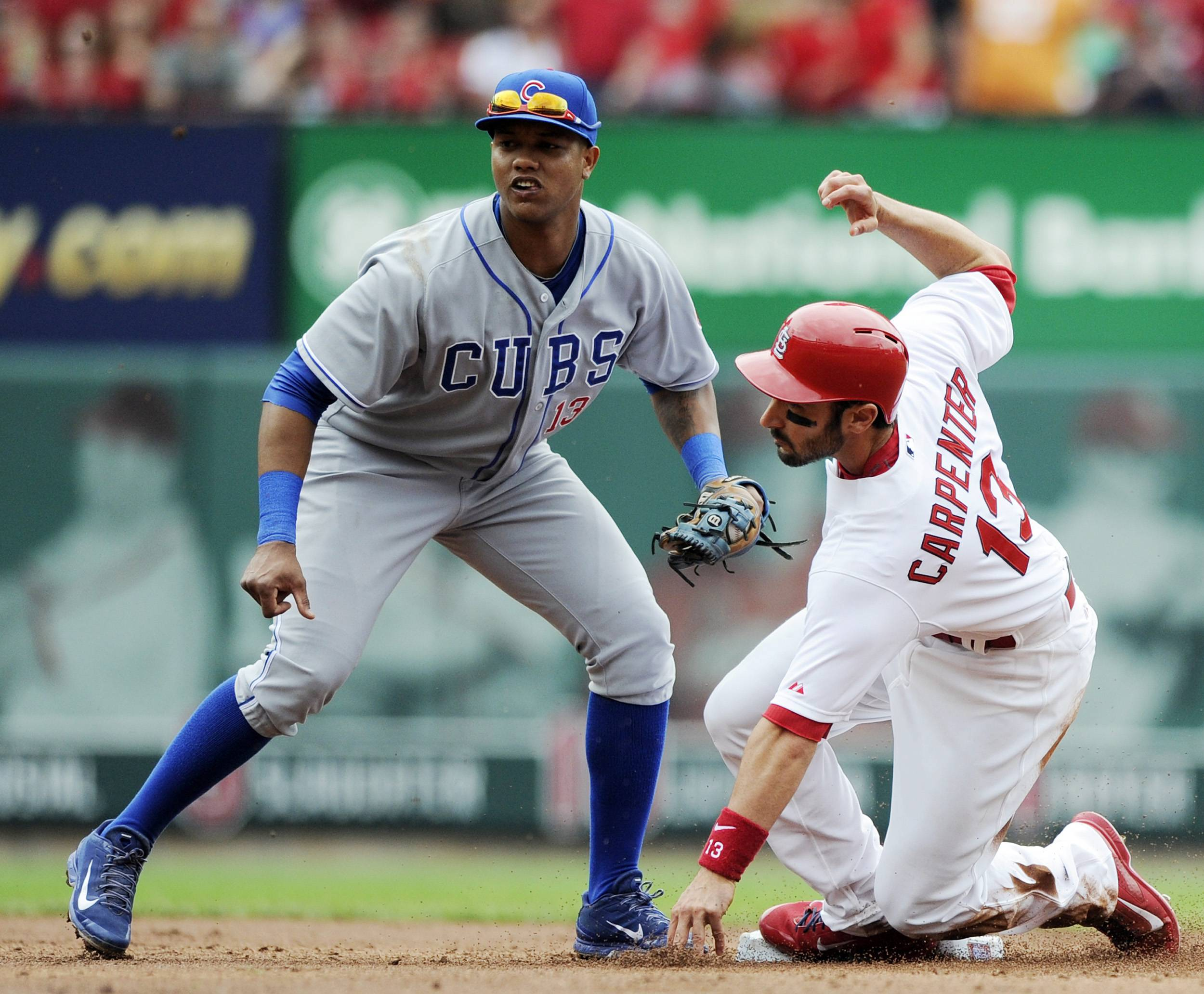 The St. Louis Cardinals' Matt Carpenter, right, steals second as the Cubs' Starlin Castro can't make the tag in the second inning of a baseball game, Sunday, April 13, 2014, in St. Louis.