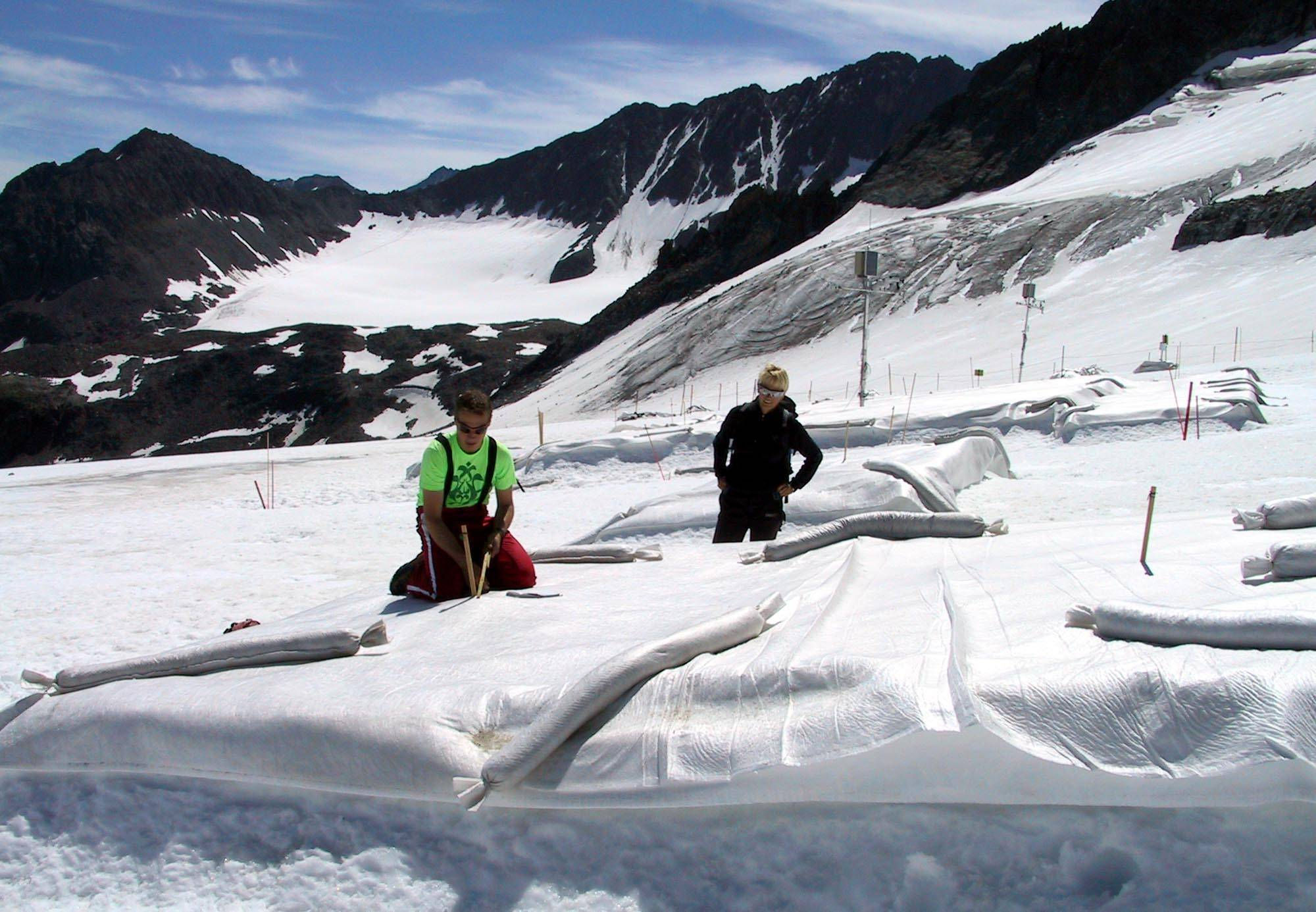 In this July 4, 2005 file photo Marc Olefs, left, and Andrea Fischer, researchers from the Innsbruck University check a field covered with white polyethylene against the backdrop of majestic jagged peaks at Eisgrat (Ice Spine) skiing station on Stubai glacier near the village of Neustift im Stubaital in the alpine Austrian province of Tyrol.