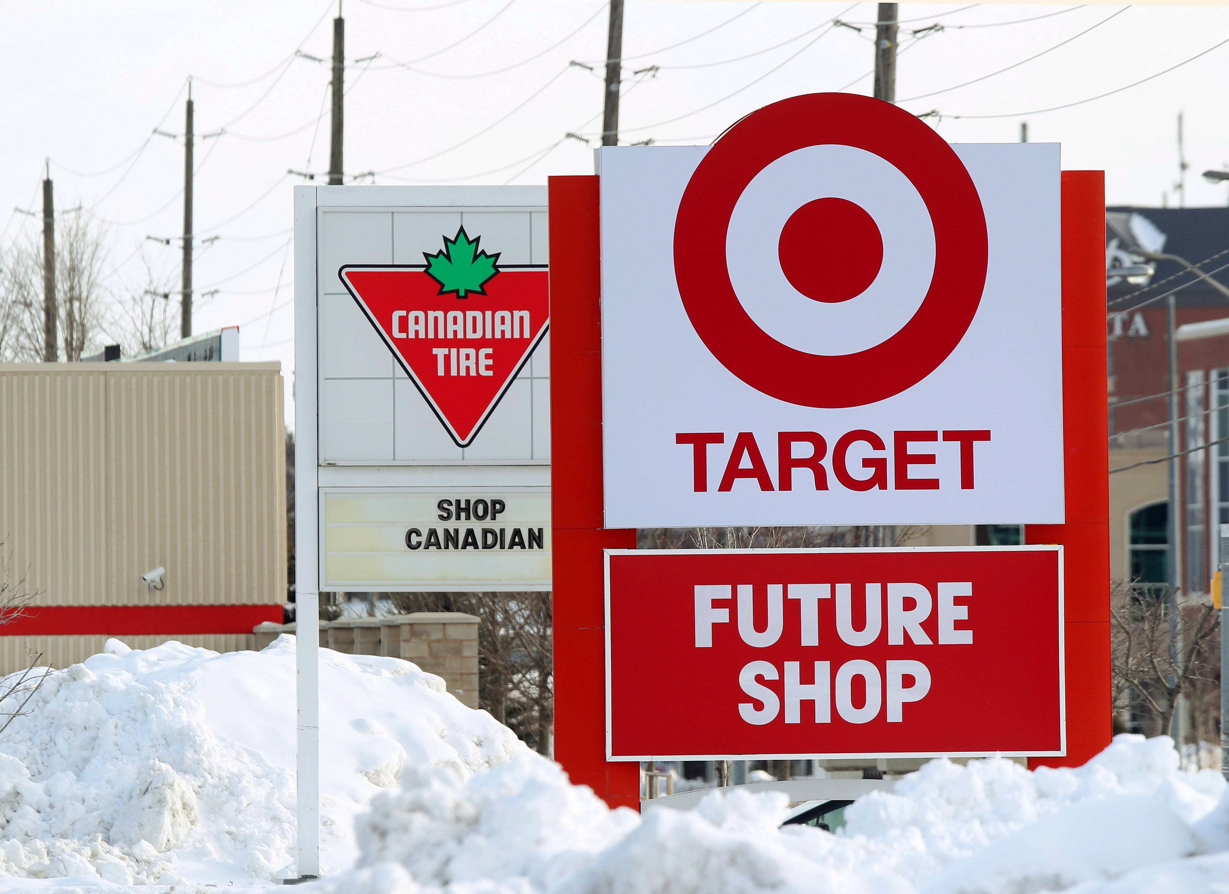In this March 4, 2013 file photo, snow is piled in the parking lot of the new Target store in Guelph, Ontario as Canadian Tire posts a Canadian message on their sign. For years, Canadians would cross the border to the U.S. to shop at Target. Exporting its cheap chic there seemed like a no-brainer. But a year after opening more than 100 stores north of the border, Target has found business isn't so easy.