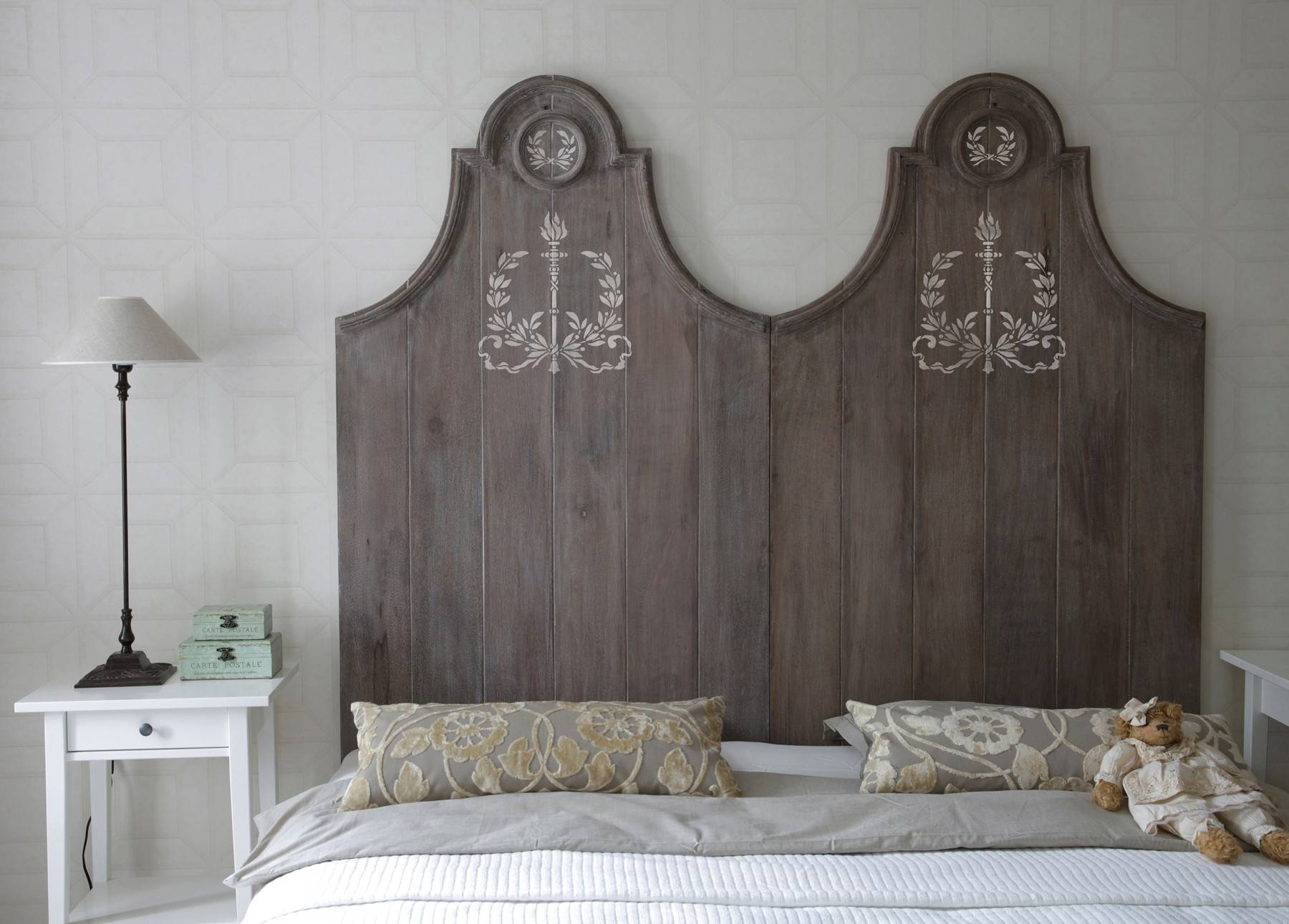 Consider use of old doors, wrought iron gates or sections of fencing as a headboard. Dress them up with a stencil drawing, or consider stenciling a pattern right onto the wall itself.