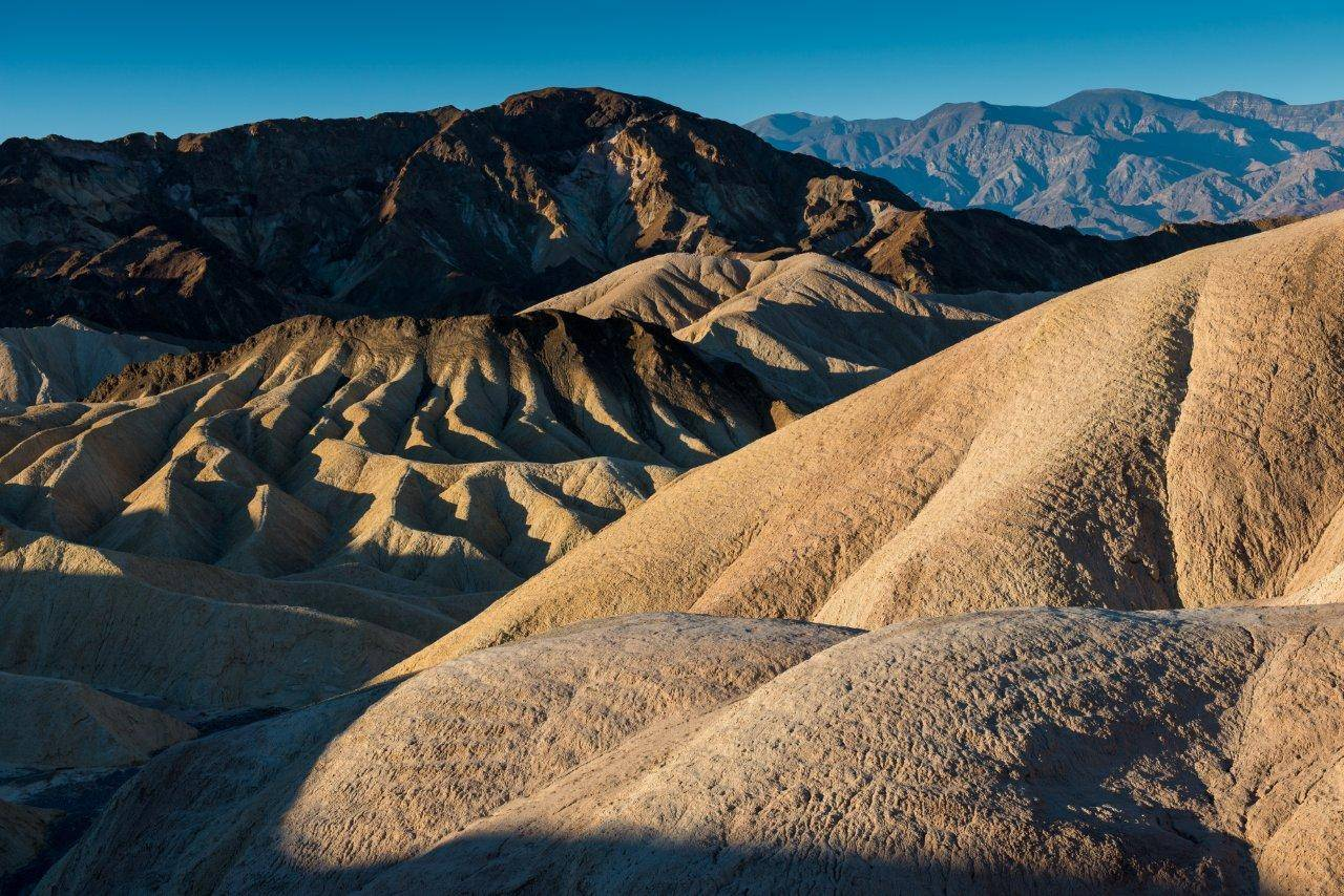 The beauty of Death Valley National Park includes a wavy rockscape in sun and shadow. The park is one of the hottest places on earth, but temperatures are less extreme in the spring than summer.