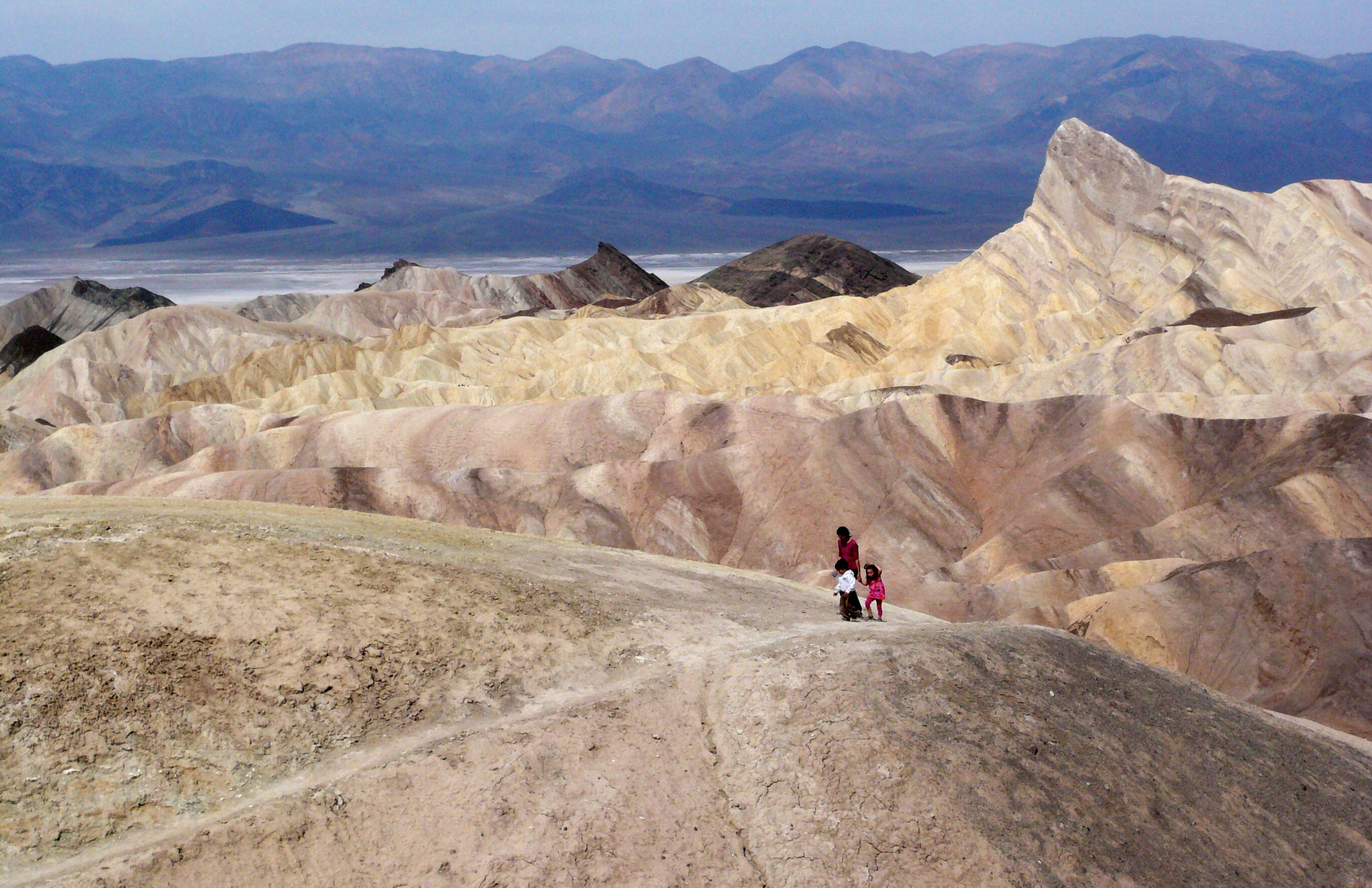 Tourists walk along a ridge at Death Valley National Park, Calif.
