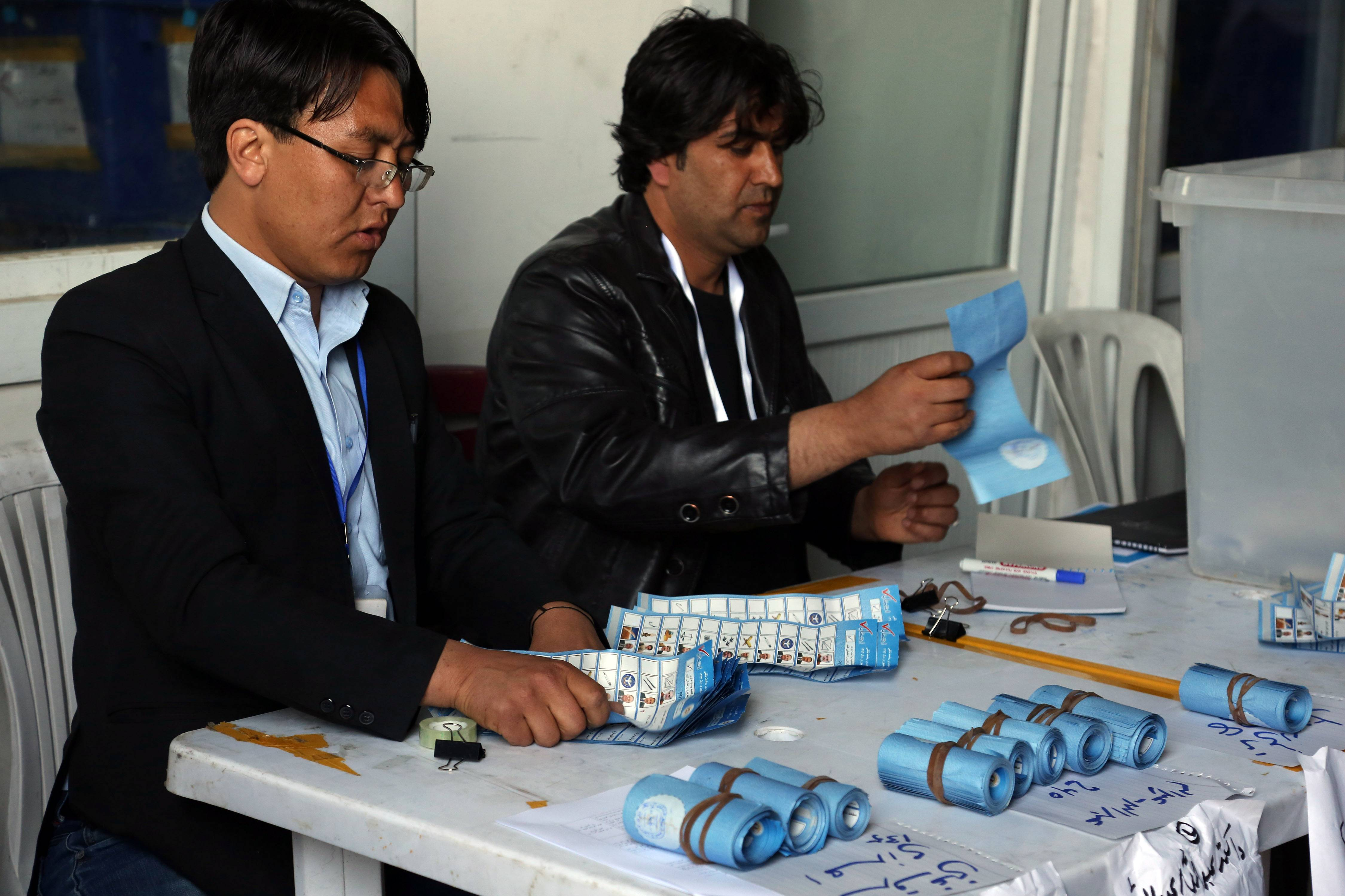 Afghan election workers counts ballots at an Independent Election Commission office in Kabul on Sunday. Partial results released Sunday in Afghanistan's crucial presidential election show a tight race between ex-foreign minister Abdullah Abdullah and former finance minister Ashraf Ghani.