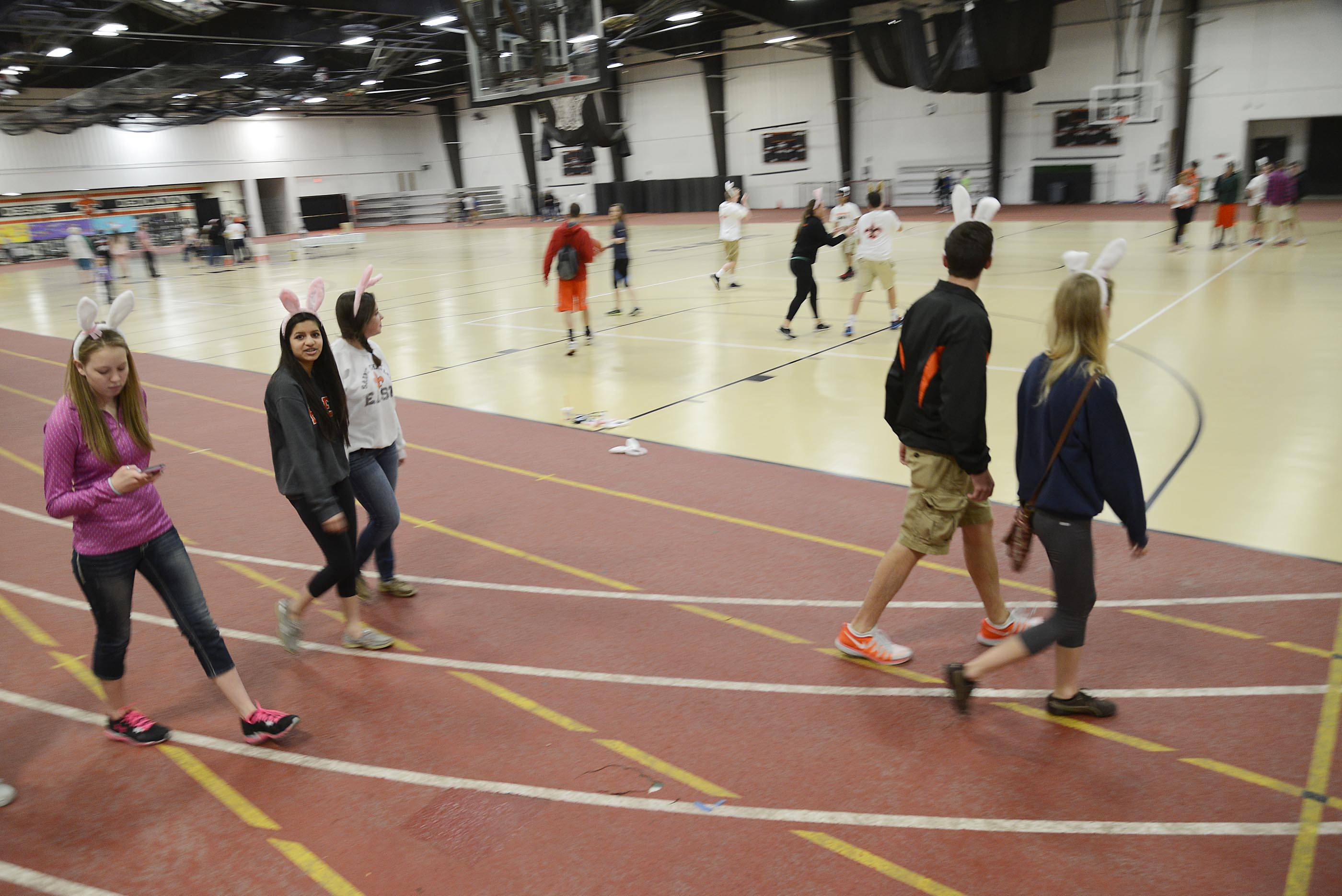 Students round the indoor track during a Juvenile Arthritis benefit walk organized by the St. Charles East High School student council Sunday at the school's Sports Center.