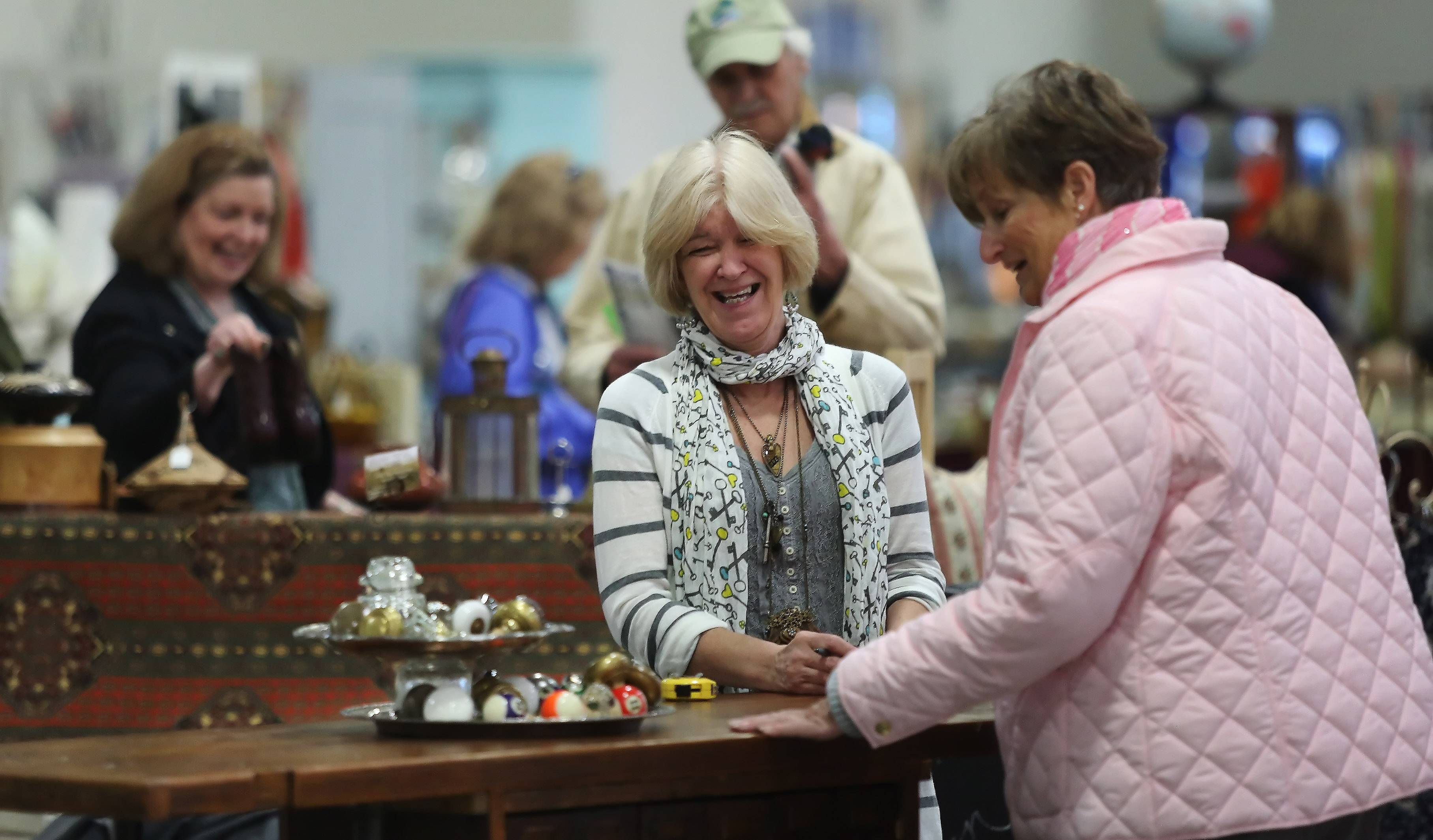 Diane Brandt of Pine Tree Primitives shares a laugh with Mary Thillens of Libertyville during the Zurko Antique and Flea Market on Sunday at the Lake County Fairgrounds in Grayslake. The monthly event features antiques, collectibles, vintage clothing and toys, sports memorabilia and more.