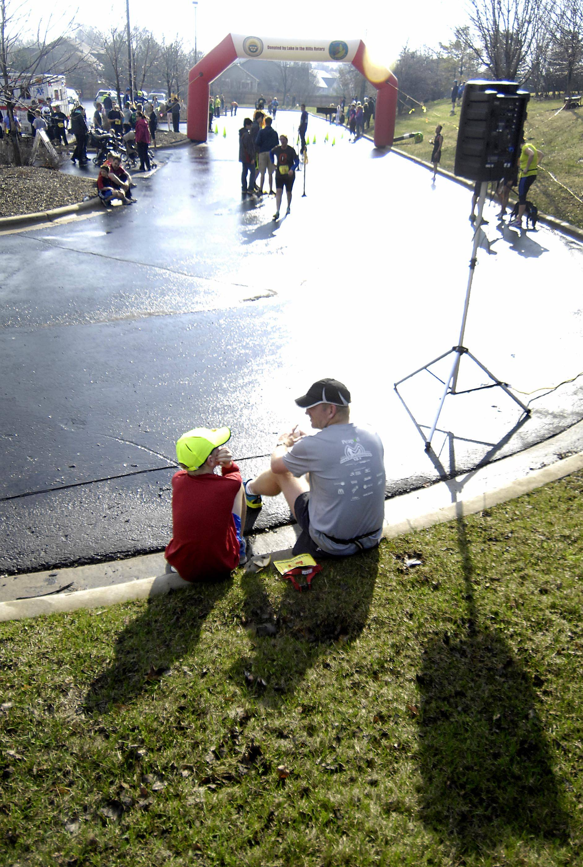 Jerry Cravens of Algonquin talks with his son Owen, 10, near the finish line Sunday morning at the 15th Run Thru The Hills 5K and 10K road races in Lake in the Hills. They both ran the 5K, with Owen finishing a minute faster than his dad.