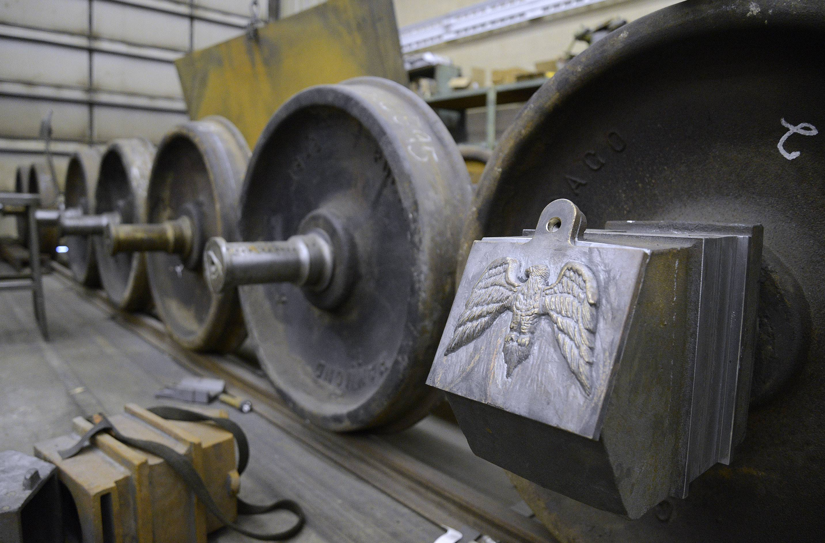 Wheel sets for a replica of Abraham Lincoln's funeral car sit in David H. Kloke's shop in Elgin. Custom made hot boxes, with a hand-designed eagle carving lid cast into metal, will cover each wheel.