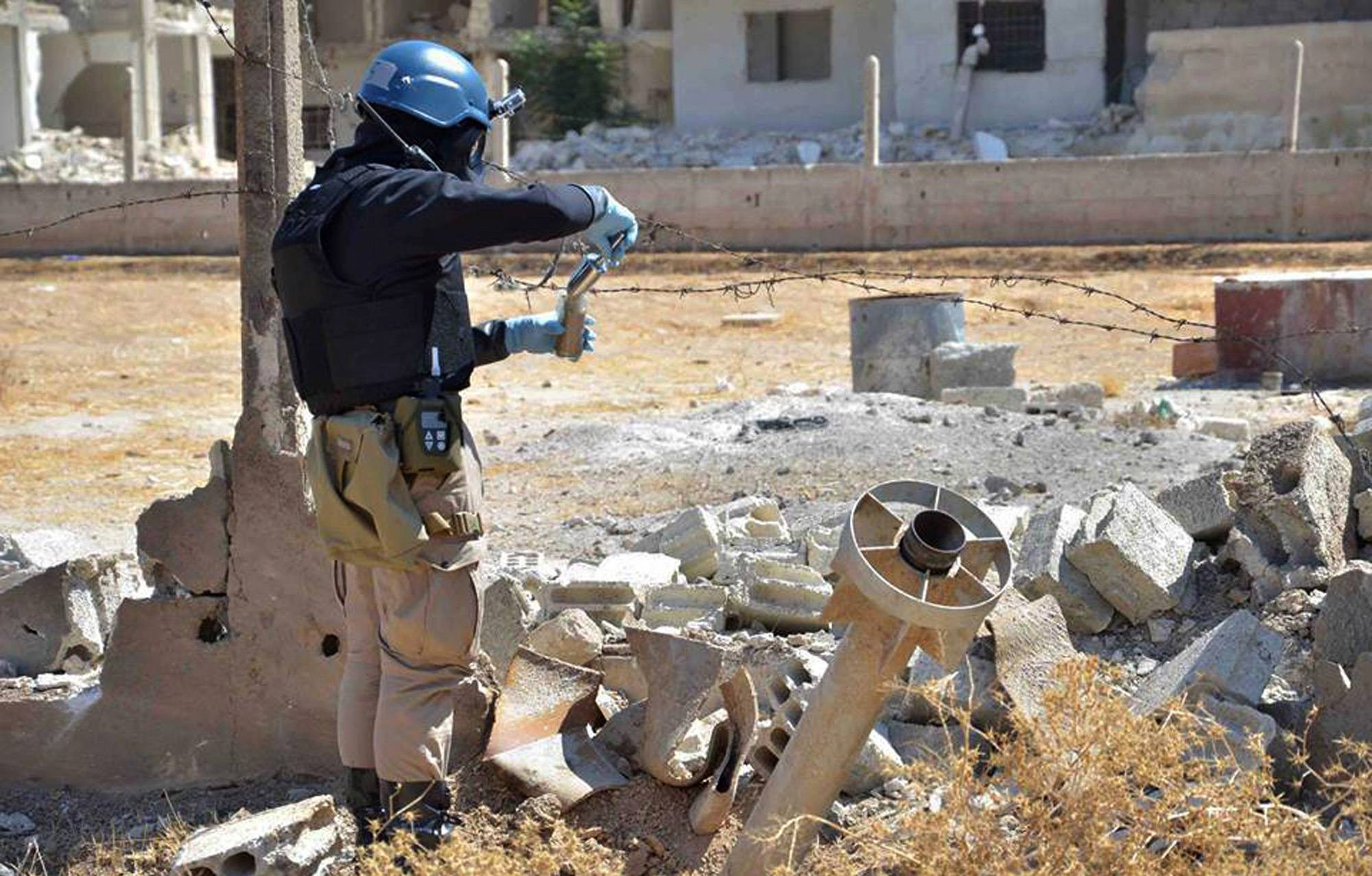 Associated Press/Wednesday, Aug. 28, 2013A member of a U.N. investigation team takes samples of sands Saturday near a part of a missile strike that is likely to be one of the chemical rockets, according to activists, in Ain Terma, Syria.