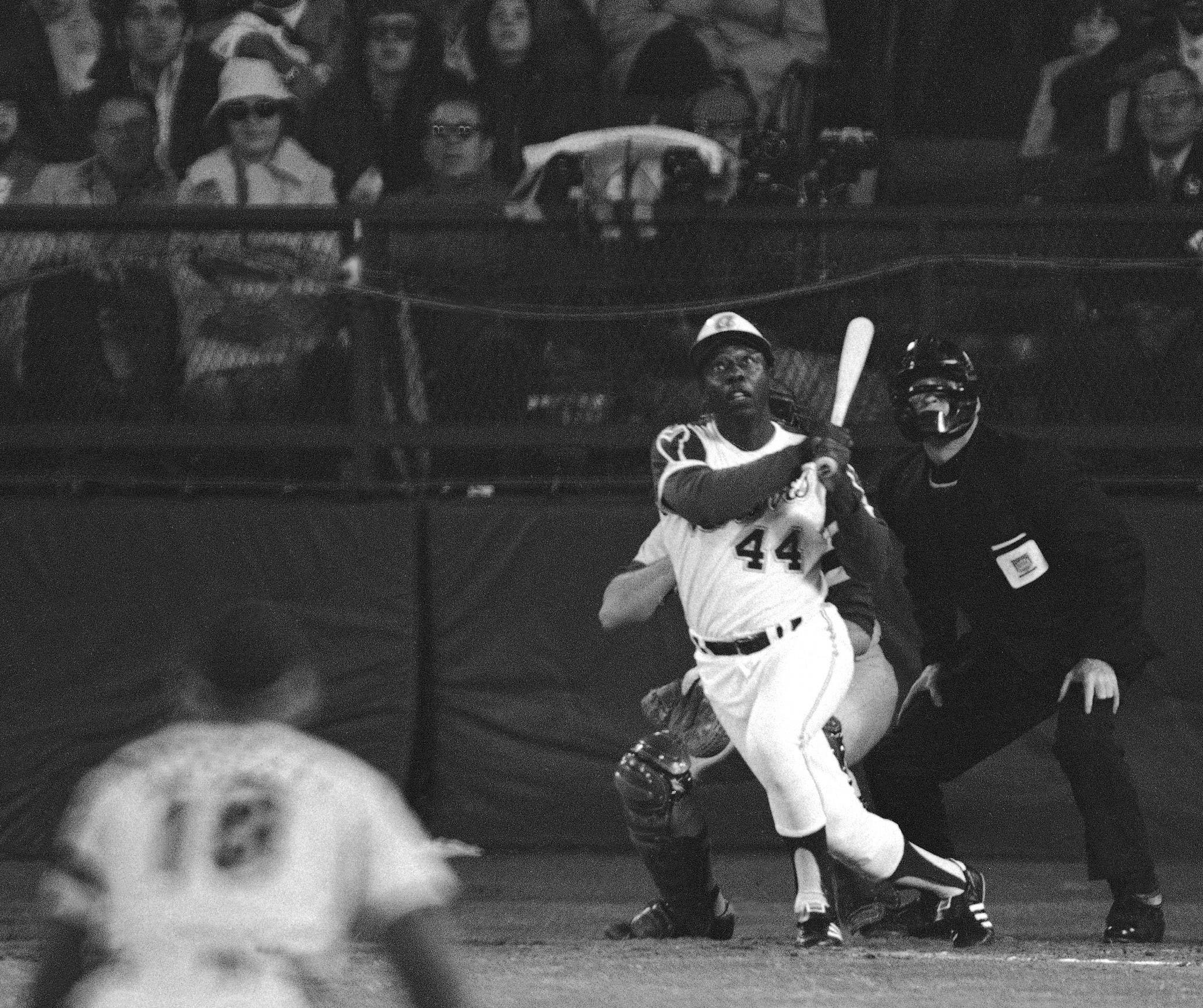 In this April 8, 1974 file photo, Atlanta Braves' Hank Aaron eyes the flight of the ball after hitting his 715th career homer in a game against the Los Angeles Dodgers in Atlanta.