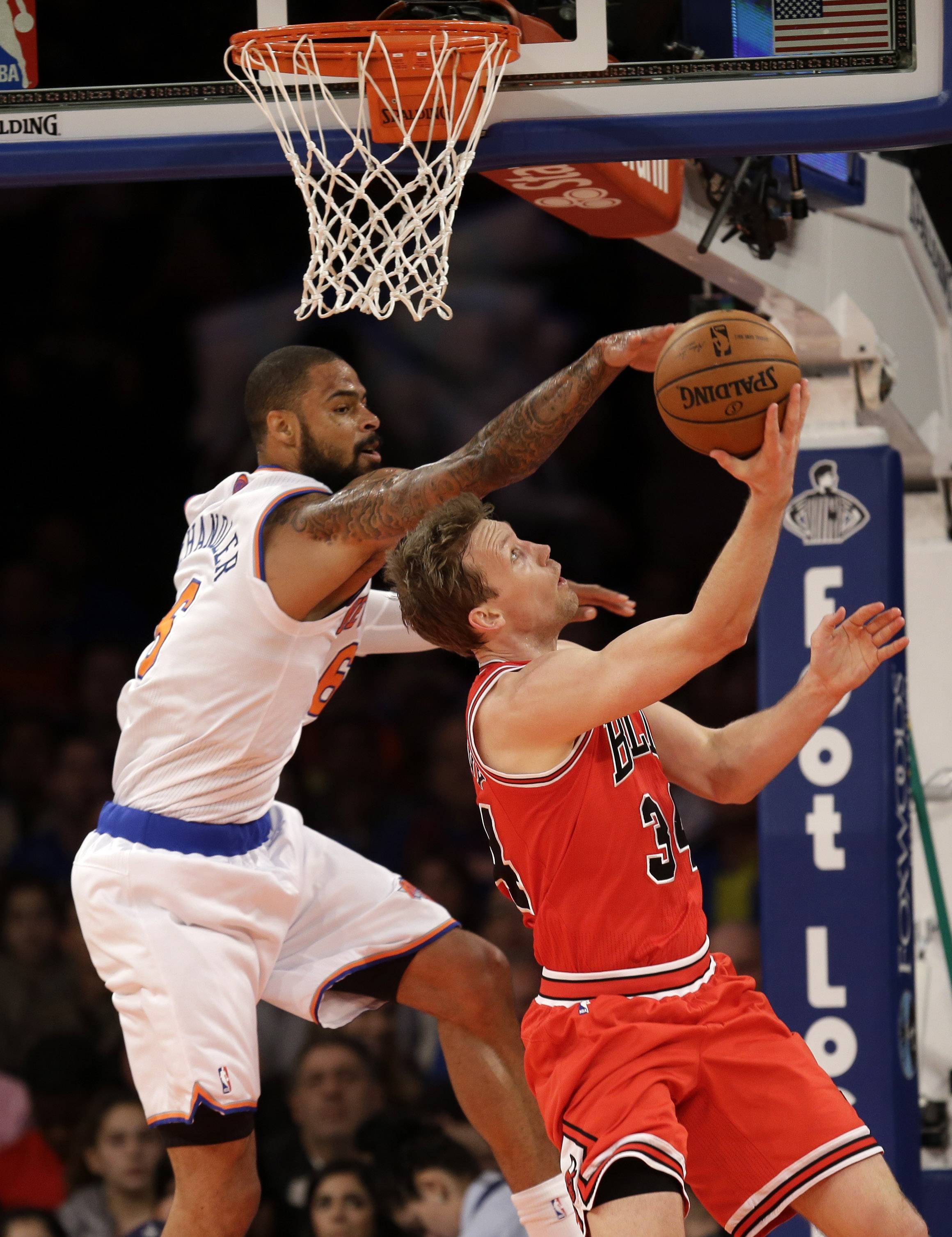 New York Knicks' Tyson Chandler, left, tries to block a shot by Chicago Bulls' Mike Dunleavy during the first half of the NBA basketball game, Sunday, April 13, 2014 in New York.
