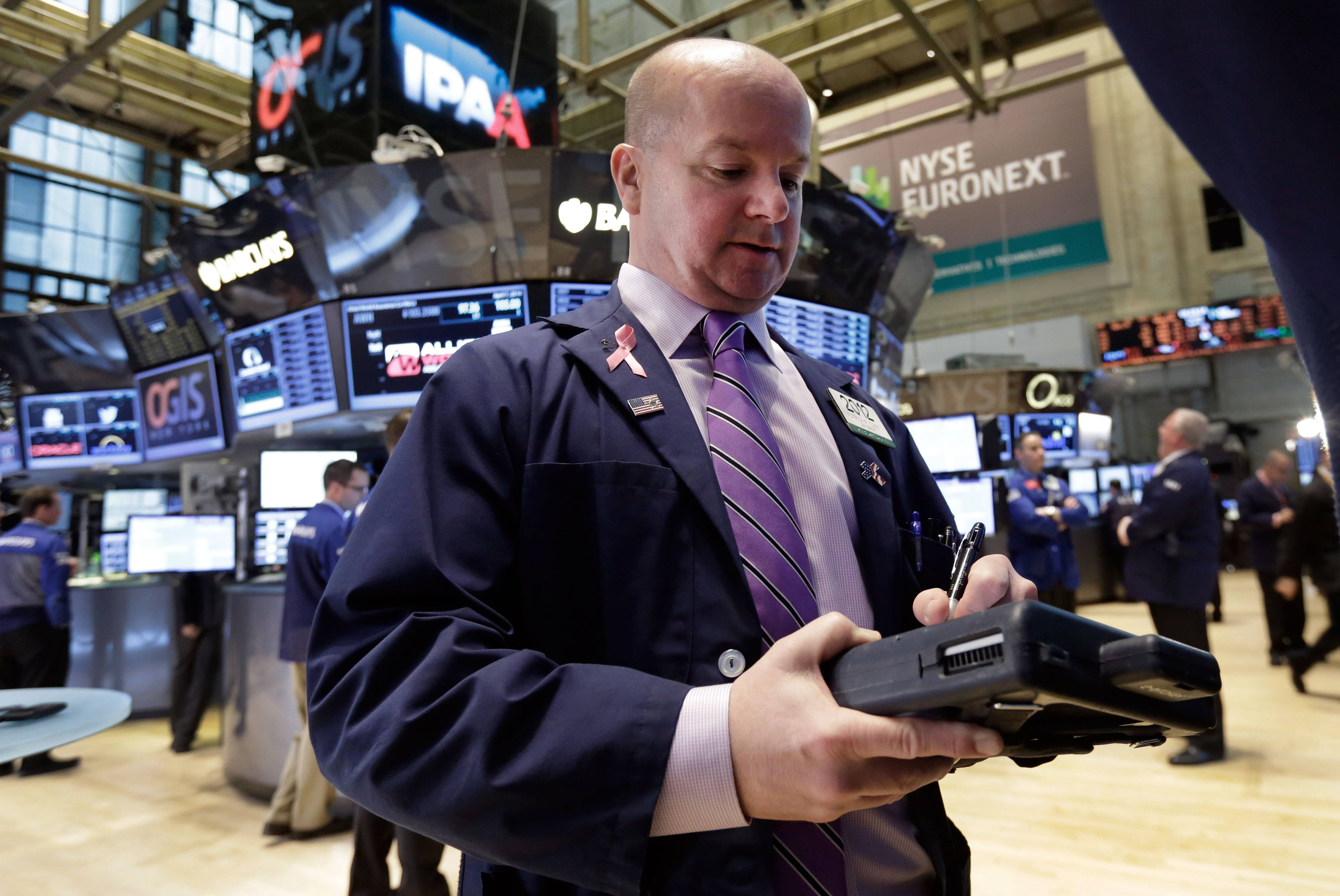 Trader Patrick Casey works on the floor of the New York Stock Exchange earlier this month. Global stock markets fell Monday amid renewed concerns about the crisis in Ukraine and forecasts of lower American corporate profits.