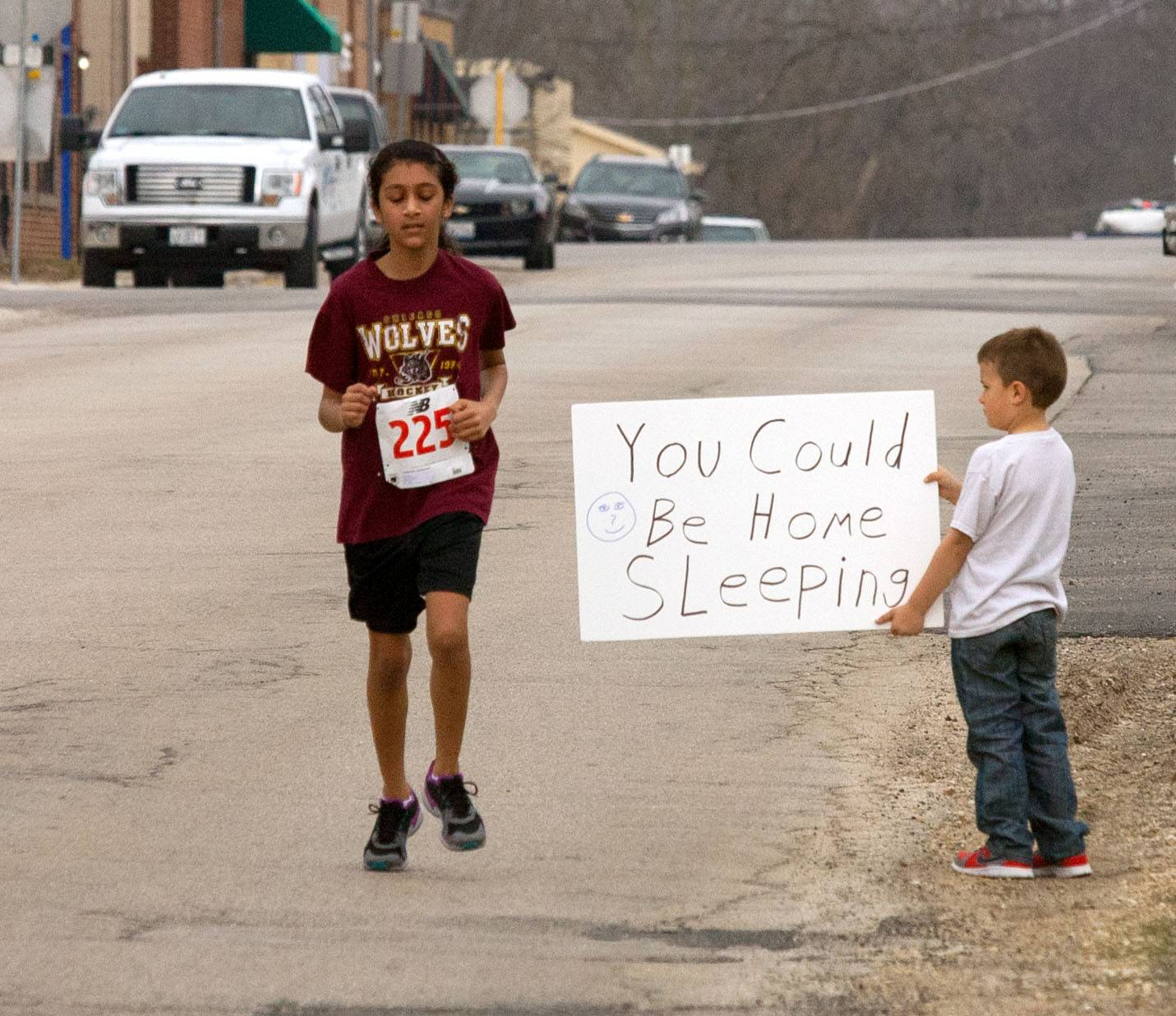 Gianni Middona, 5, of Elburn holds an encouraging sign for Cimmy Nakum, 12, of Elburn, who finishes the 10th annual Dewey Dash race, held Sunday in downtown Elburn. According to a race results website, Cimmy took first place in her age division in the 5K.