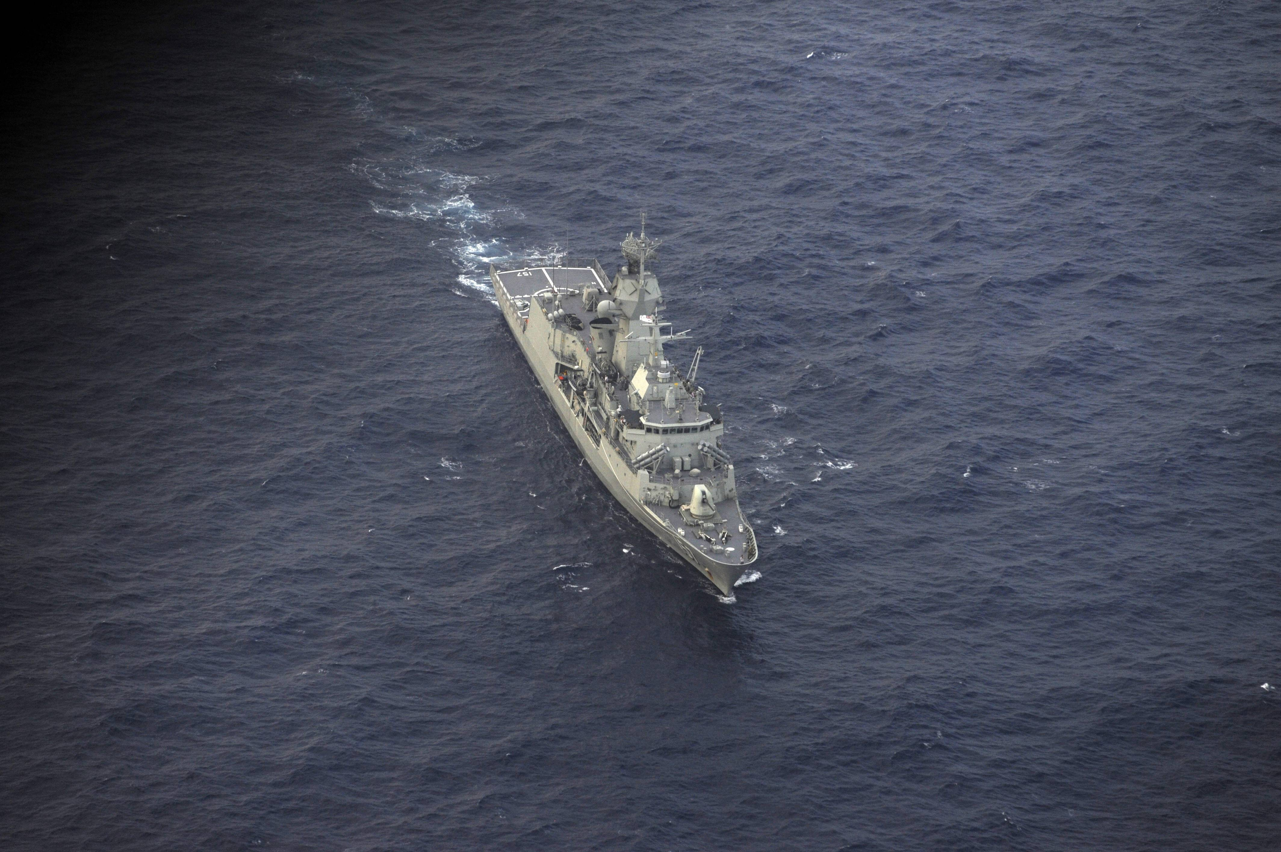 Australian ship HMAS Perth sails into position to retrieve a red object spotted by the RNZAF plane during the search for debris from missing Malaysia Airlines Flight 370, in the Indian Ocean off the coast of western Australia on Sunday. The hunt for the missing Malaysian airliner continued to focus Monday on a search for weakening radio signals from deep beneath the waves despite mounting evidence that the batteries in the plane's all-important black boxes may finally have died.
