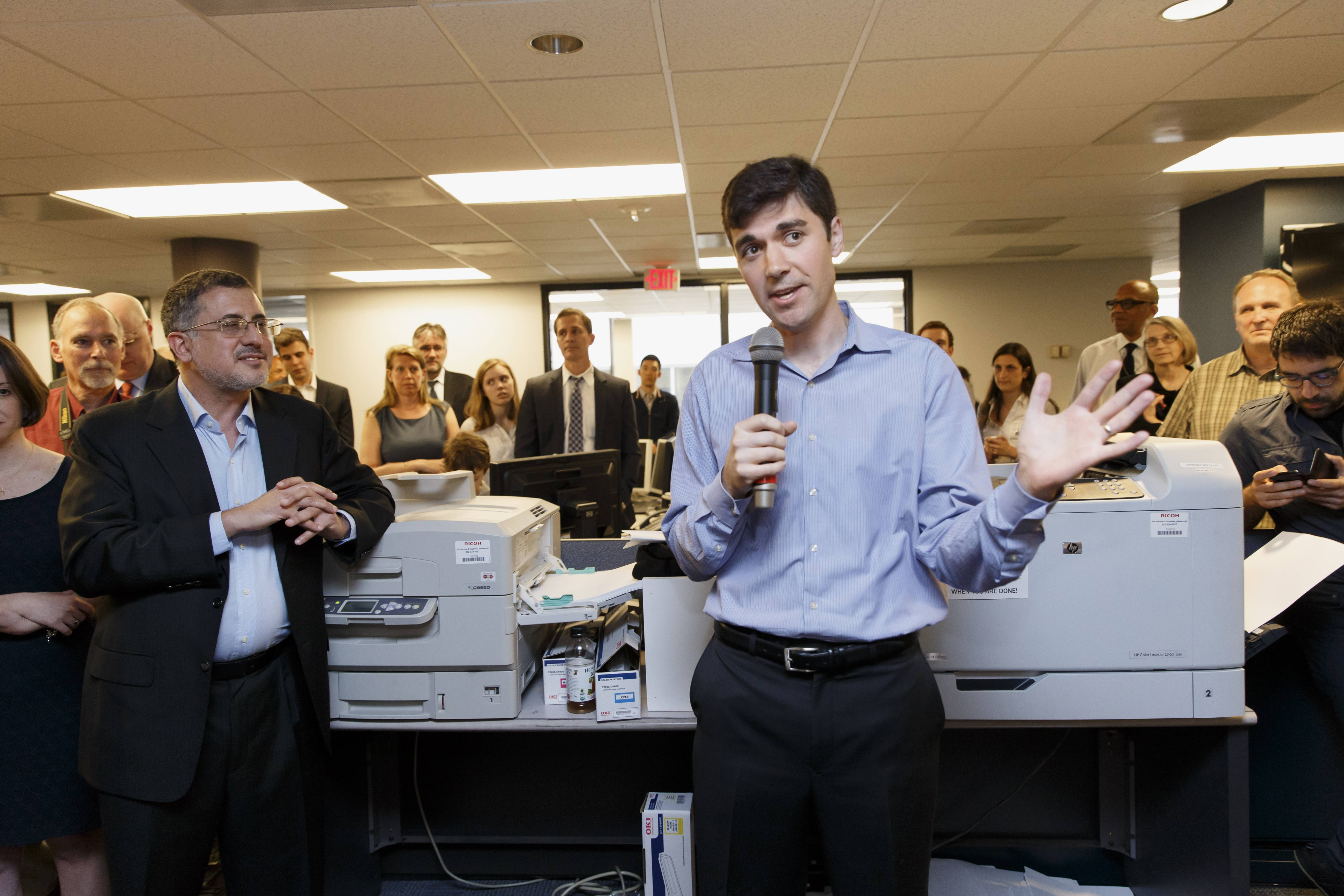 Washington Post writer Eli Saslow, center, speaks to his newsroom colleagues Monday after the announcement that he was awarded the Pulitzer Prize for Explanatory Reporting for his reporting on the prevalence of food stamps in post-recession America.