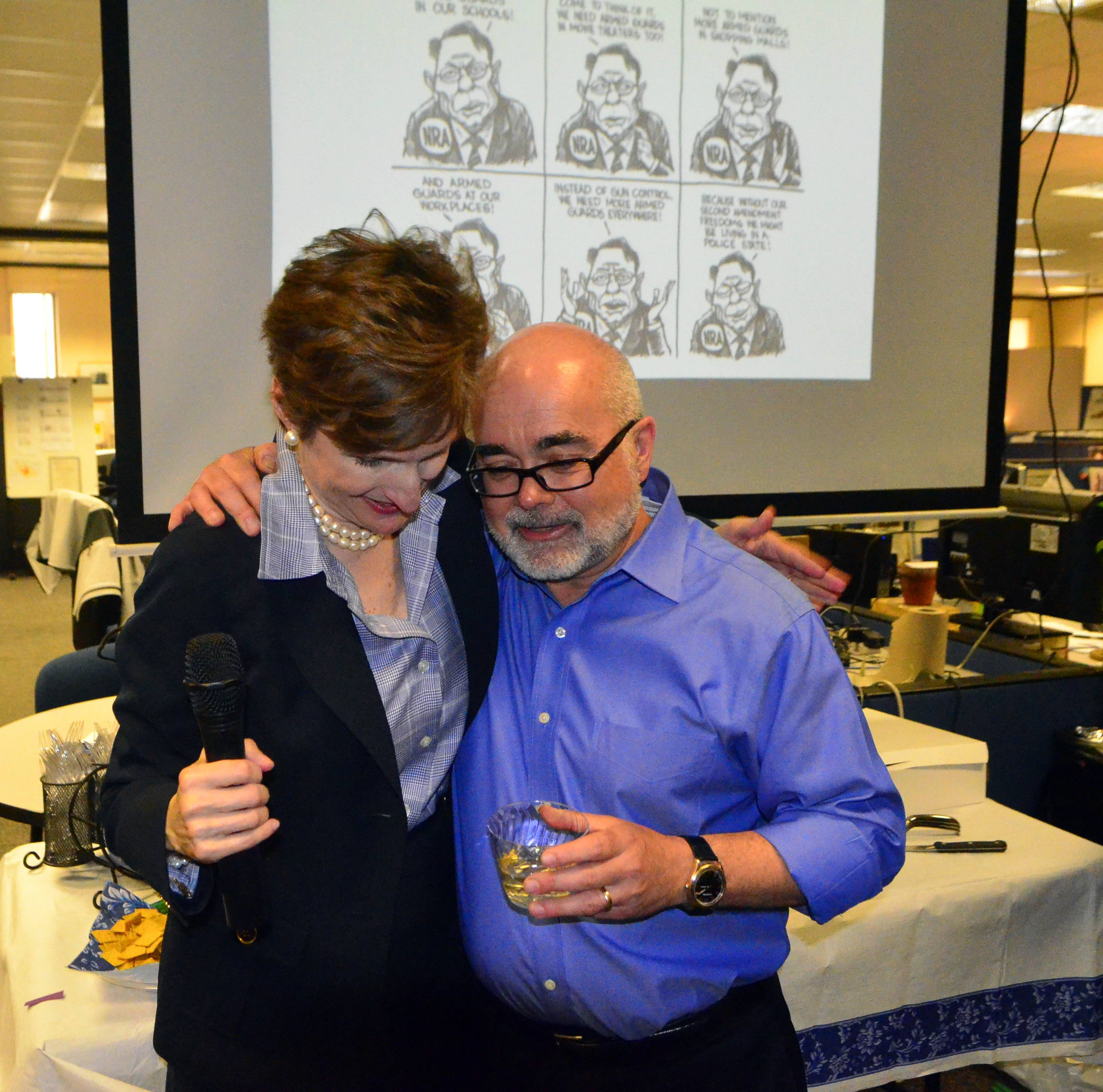 Charlotte Observer Publisher Ann Caulkins gives a hug to editorial cartoonist Kevin Siers in the newsroom Monday after it was announced that Siers had been awarded the Pulitzer Award for Editorial Cartooning.