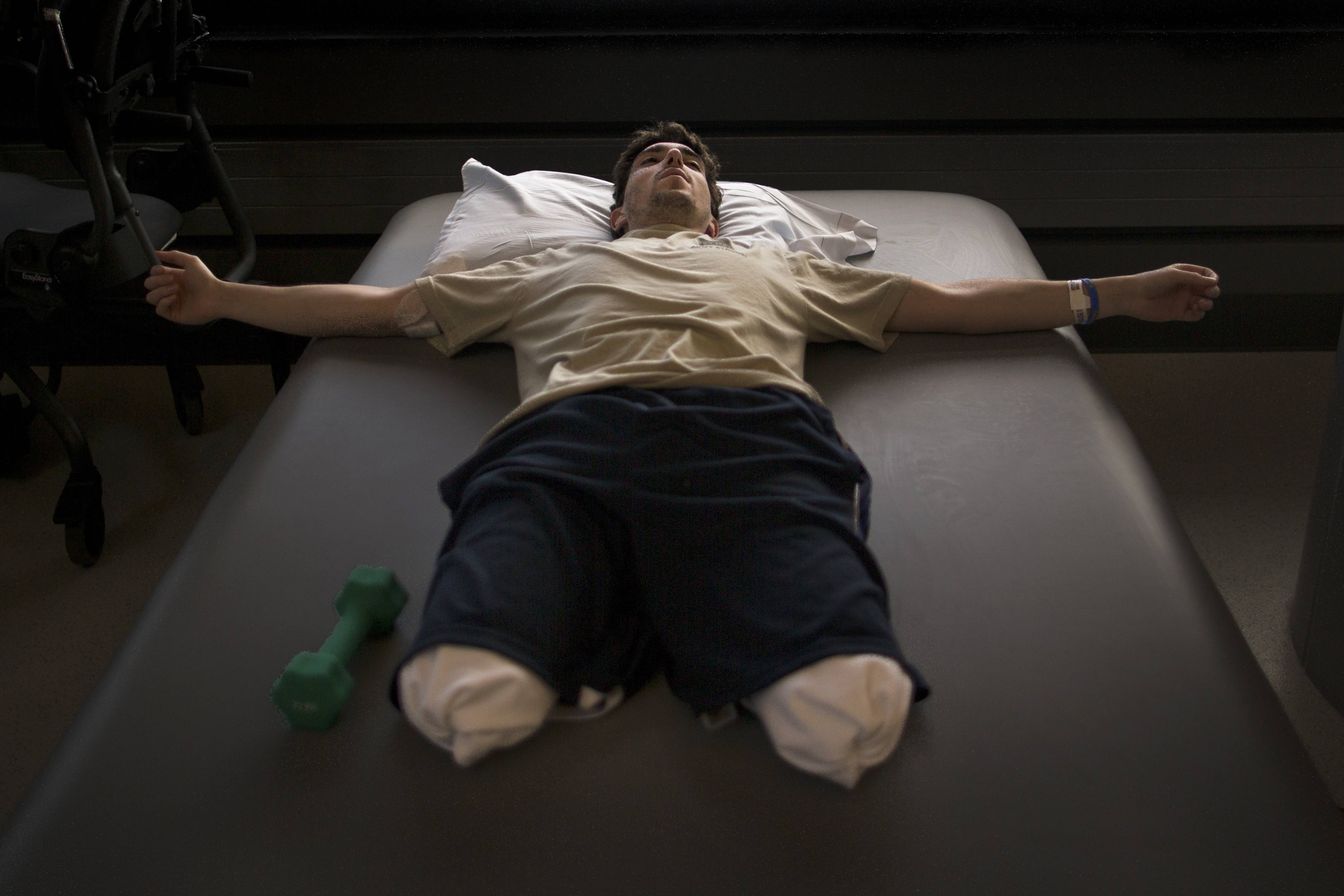 Jeff Bauman, who lost his lower legs in the Boston Marathon bombings, rests between occupational therapy sessions at Spaulding Rehabilitation Hospital in Boston, May 8, 2013. Bauman went to the Boston Marathon to see his girlfriend run, but now his supporters are watching his plight to walk again after he lost his legs in the bombing. New York Times photographer Josh Haner was awarded the 2014 Pulitzer Prize for feature photography.