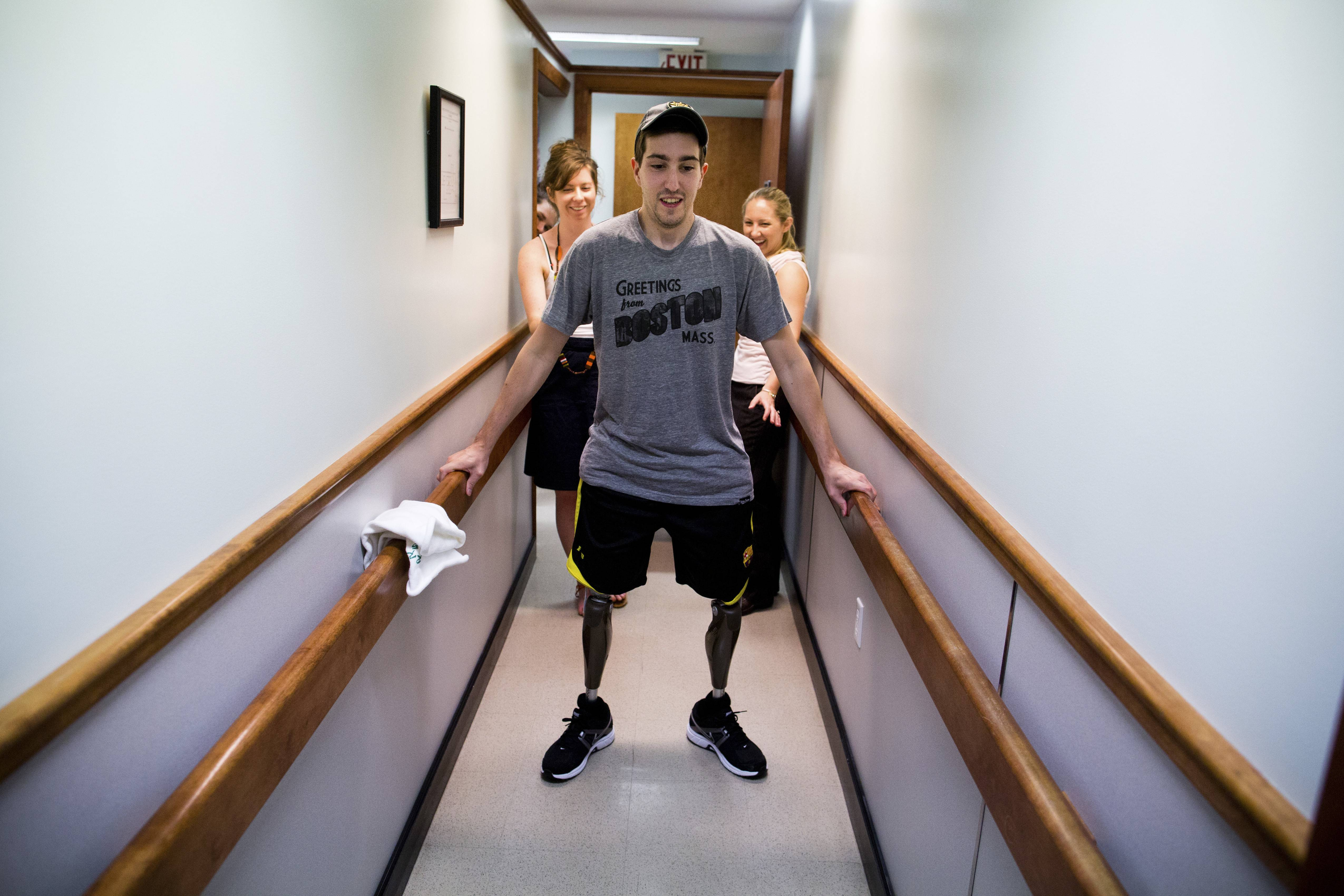 Jeff Bauman, who lost his lower legs in the Boston Marathon bombings, walks on his own for the first time since the marathon at a final fitting for his prosthetic legs. The knees in Bauman's new legs have microprocessors that can be programmed to follow his gait, to swing as he steps. Bauman's girlfriend Erin Hurley, left, and prosthetist Julianne Mason watch from behind.