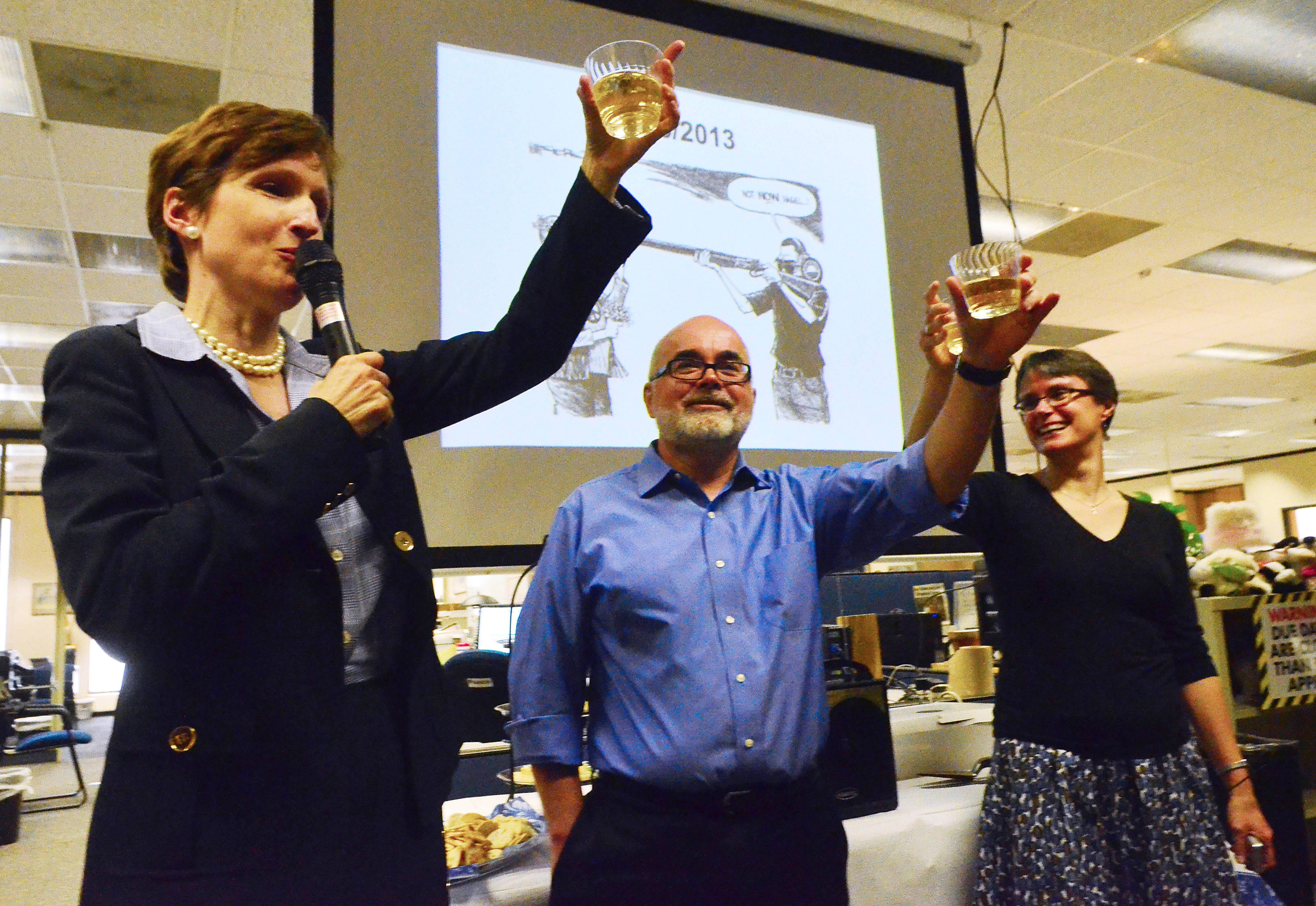 "Charlotte Observer Publisher Ann Caulkins, left, gives a toast to editorial cartoonist Kevin Siers and his wife, Jean Blish Siers in the newsroom Monday after it was announced that Siers had been awarded the Pulitzer Award for editorial cartooning. Siers received the award for his ""thought-provoking cartoons drawn with a sharp wit and bold artistic style."""