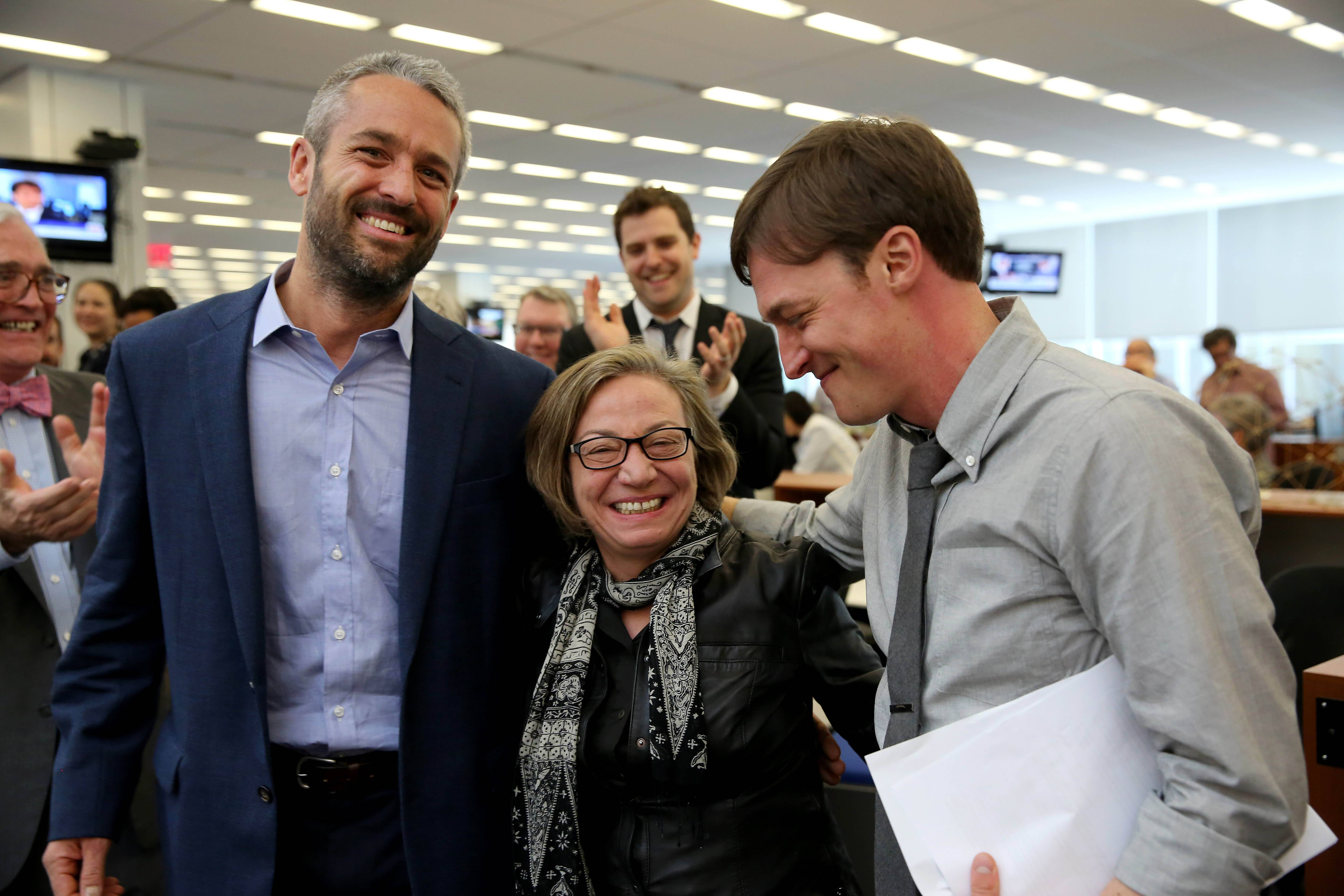 Michele McNally, center, director of photography and assistant managing editor of The New York Times, is flanked by photographers Tyler Hicks, left, and Josh Haner after it was announced in the New York newsroom Monday that Hicks and Haner had won Pulitzer Prizes.