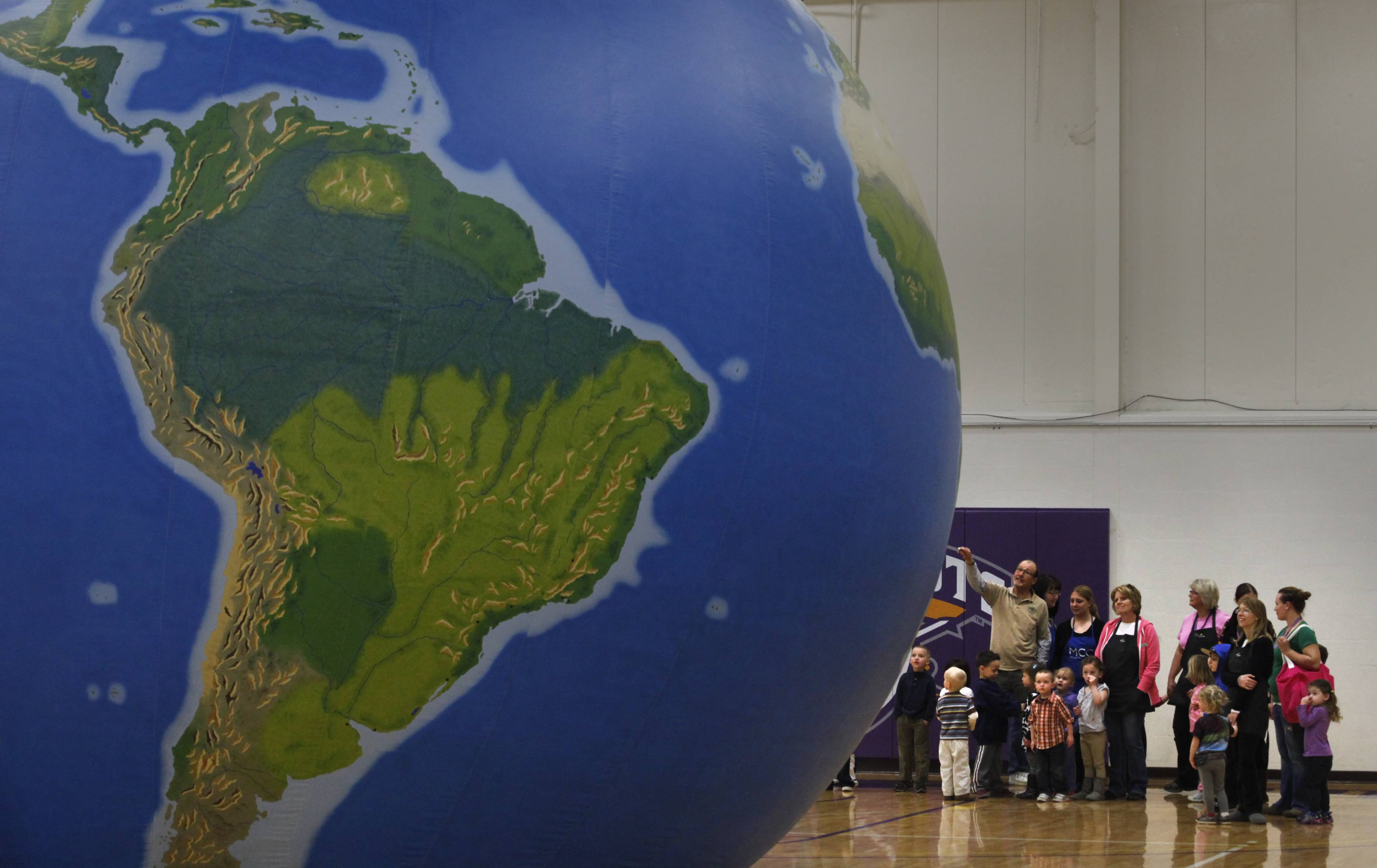 McHenry County College Children's Learning Center students and their teachers get a tour of the outside of the GeoSphere before heading inside the inflatable globe for a geography lesson Monday in Crystal Lake.