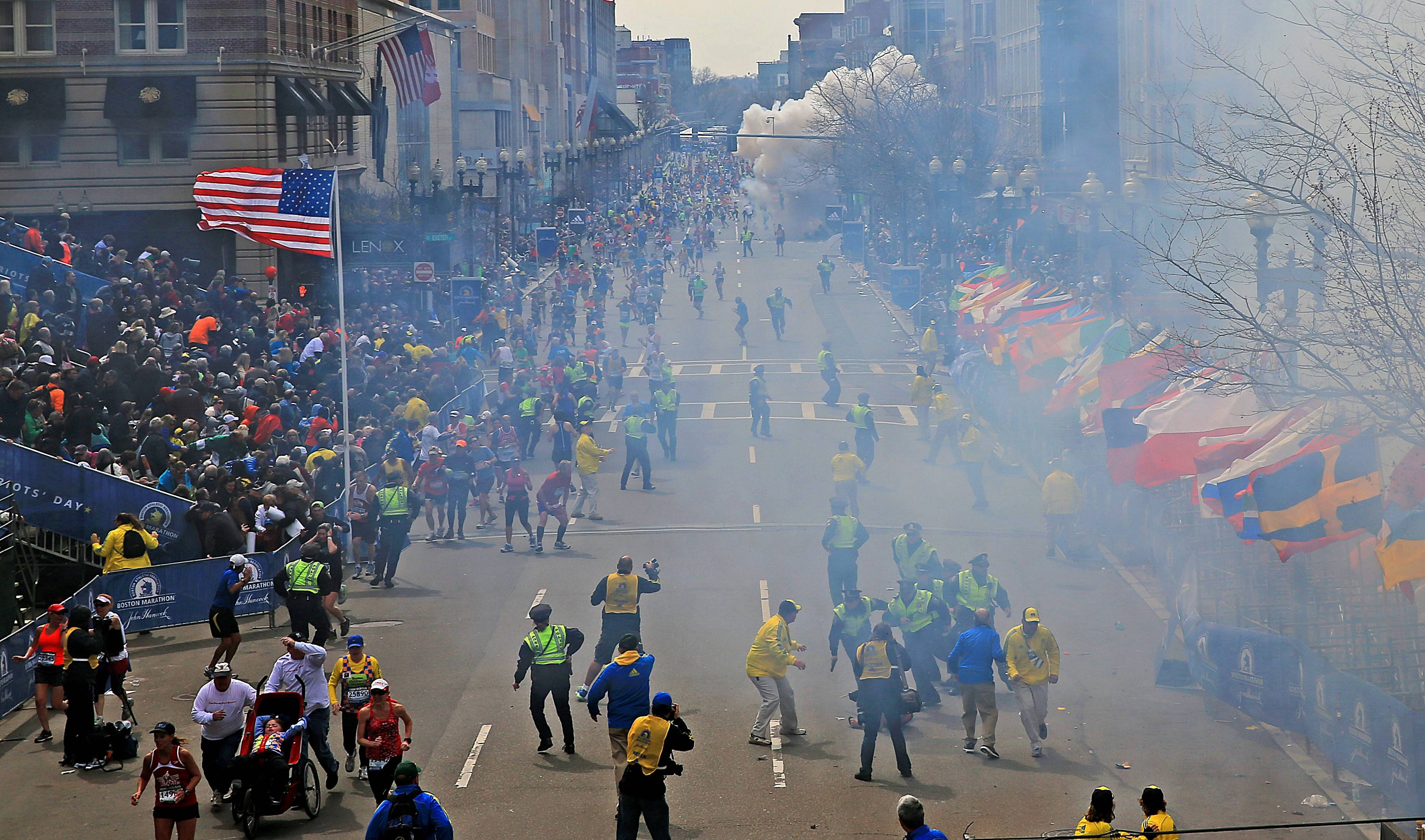 People react as an explosion goes off near the finish line of the Boston Marathon on April 15, 2013. A year after the terror attack, some questions remain unanswered.