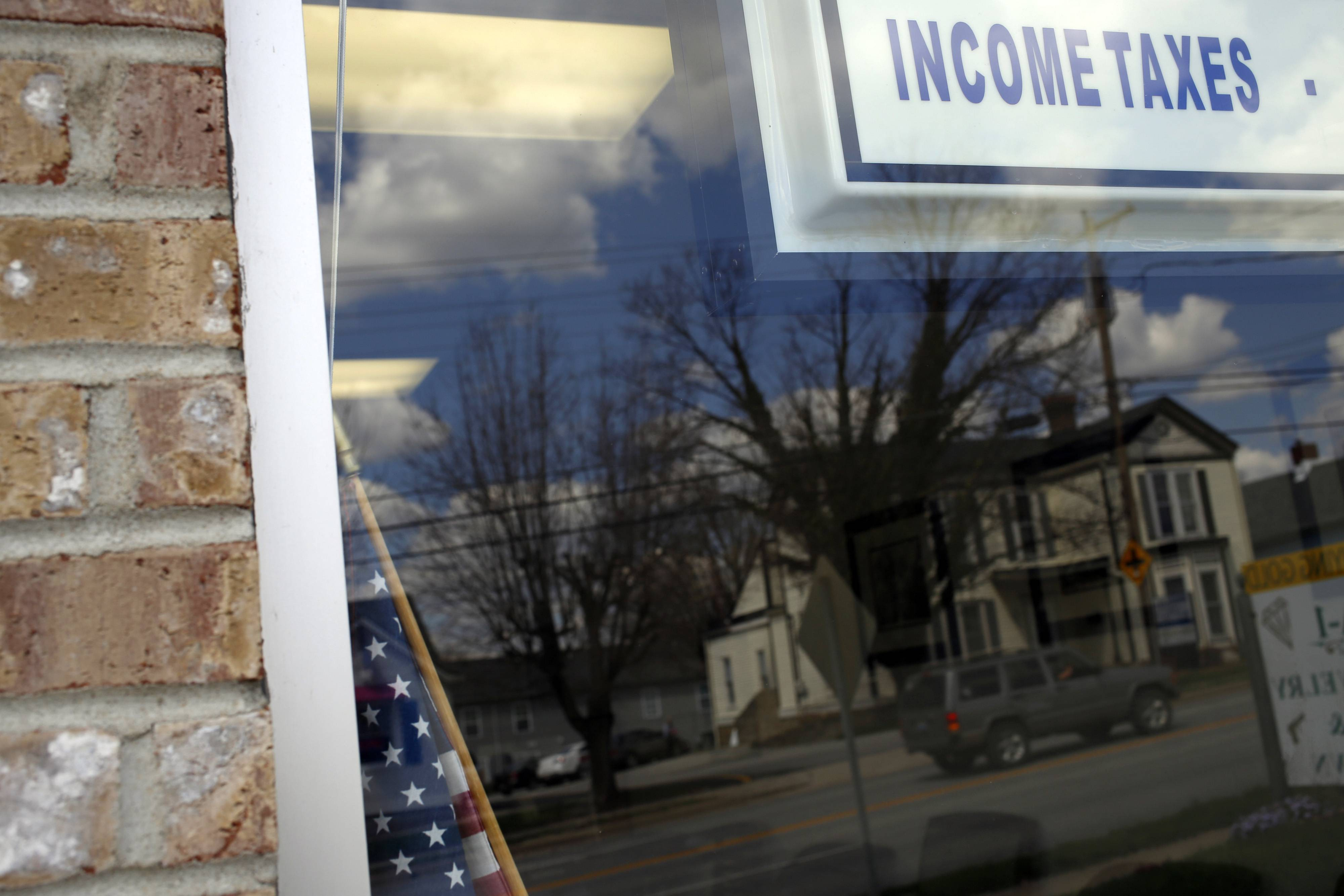 An income tax sign hangs in the window of Tax Pros USA in La Grange, Ky. The deadline for filing federal income tax returns to the Internal Revenue Service is Tuesday.