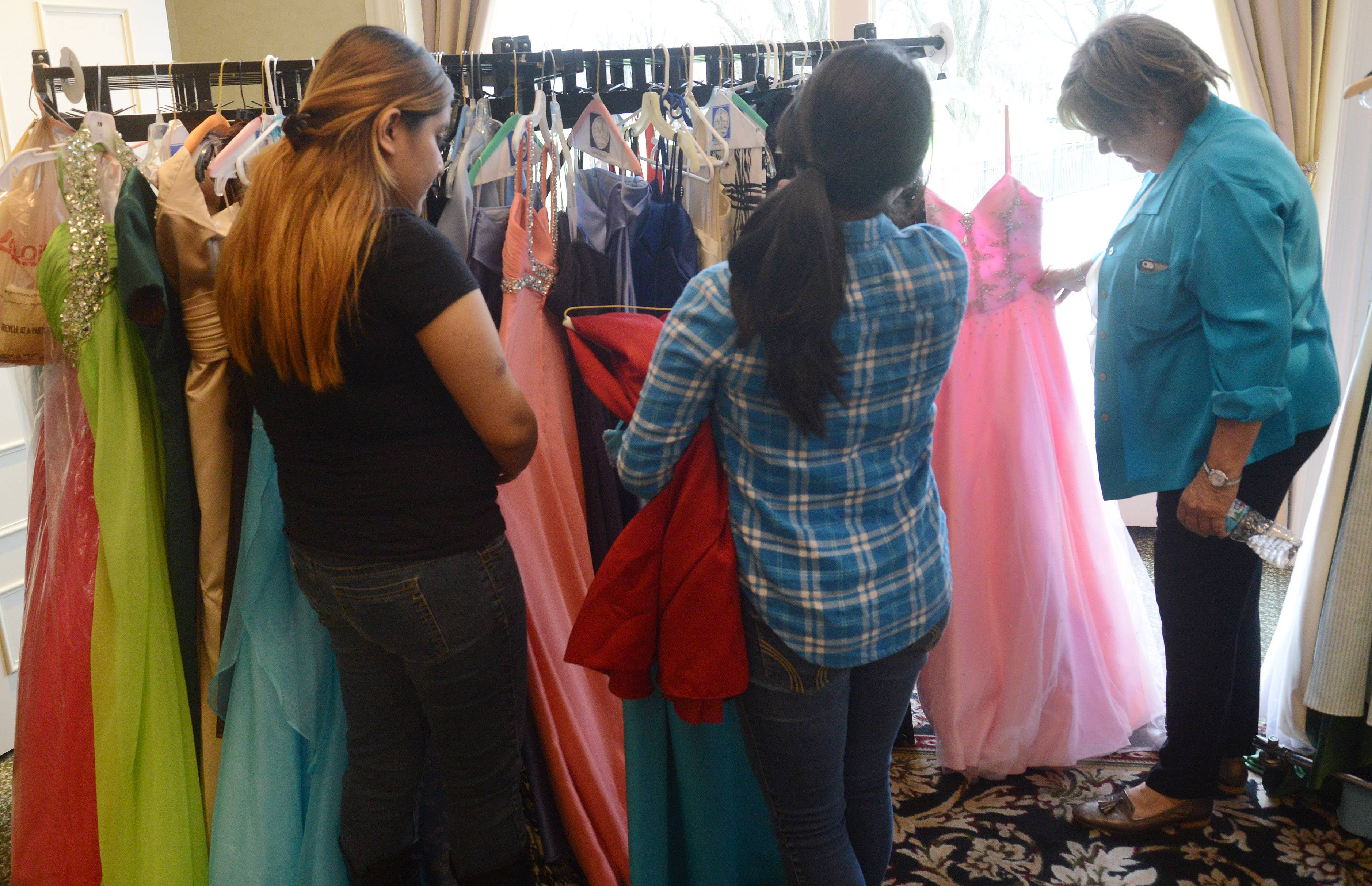 Michaelene Roark, president of the Women's Club of Rolling Green Country Club in Arlington Heights, right, helps students from District 214 pick out prom dresses and shoes.