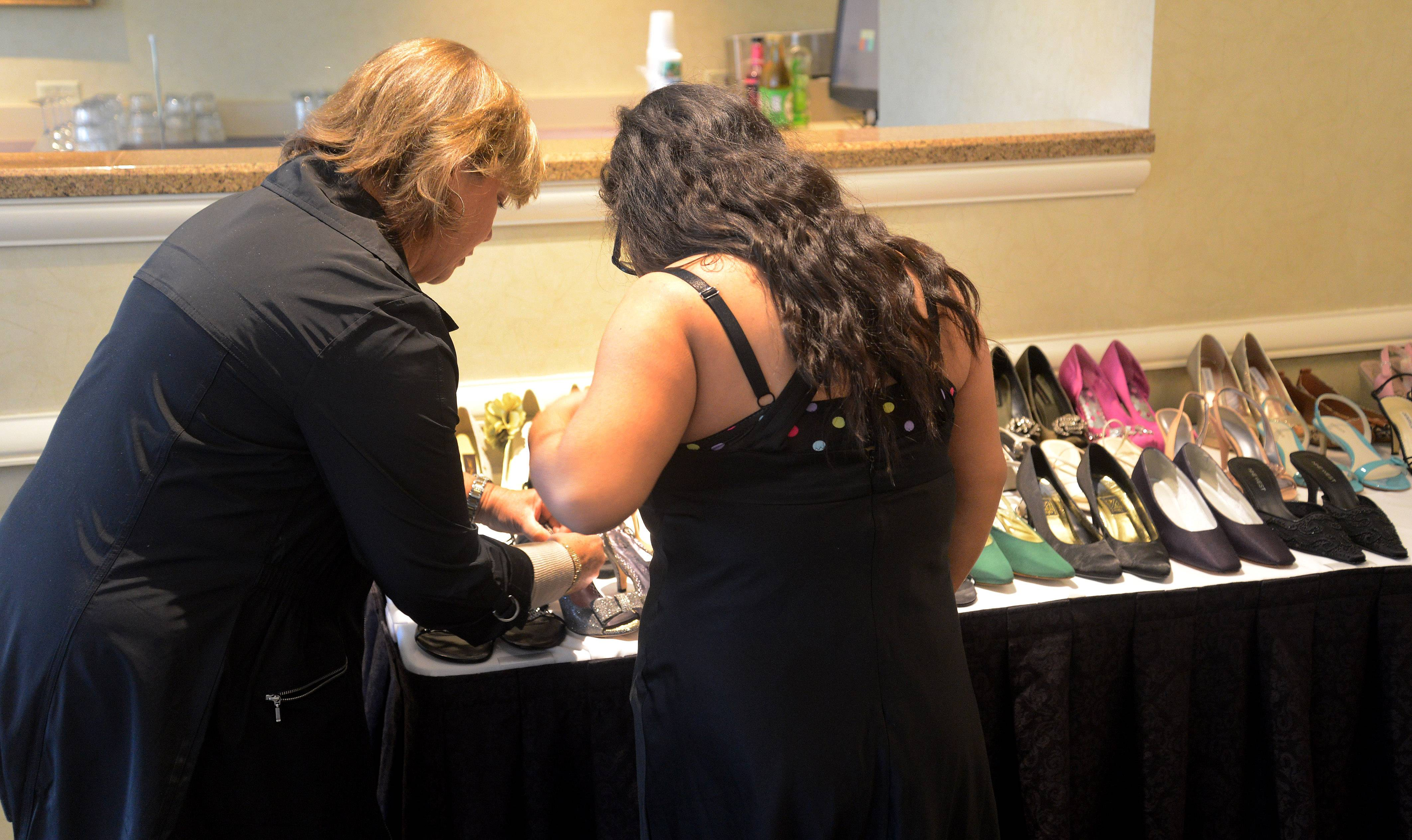 A volunteer helps a student pick out shoes.