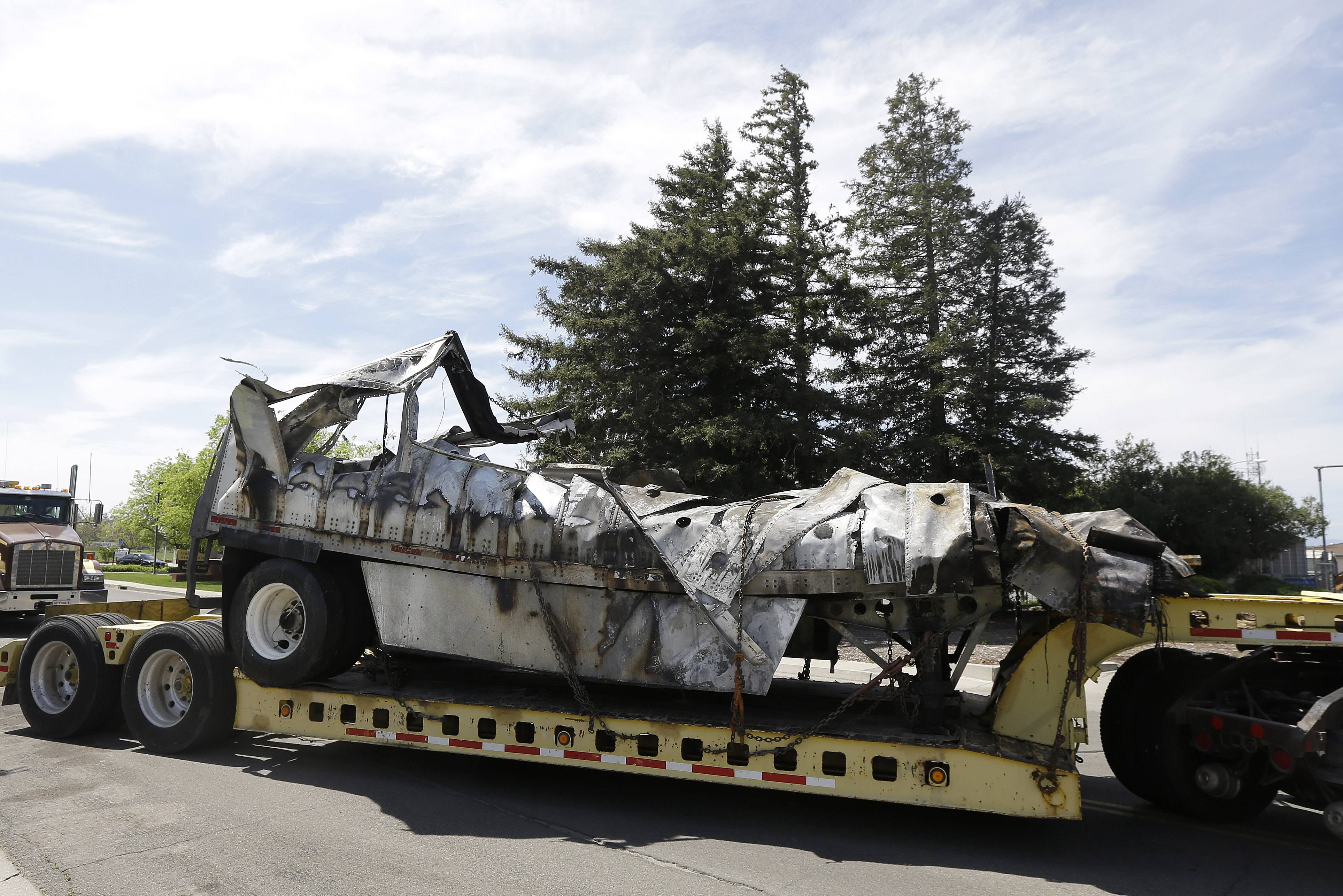 The demolished remains of a FedEx truck are towed Friday into a CalTrans maintenance station in Willows, Calif. At least ten people were killed and dozens injured in the fiery crash on Thursday between a FedEx truck and a bus carrying high school students on a visit to a Northern California college.