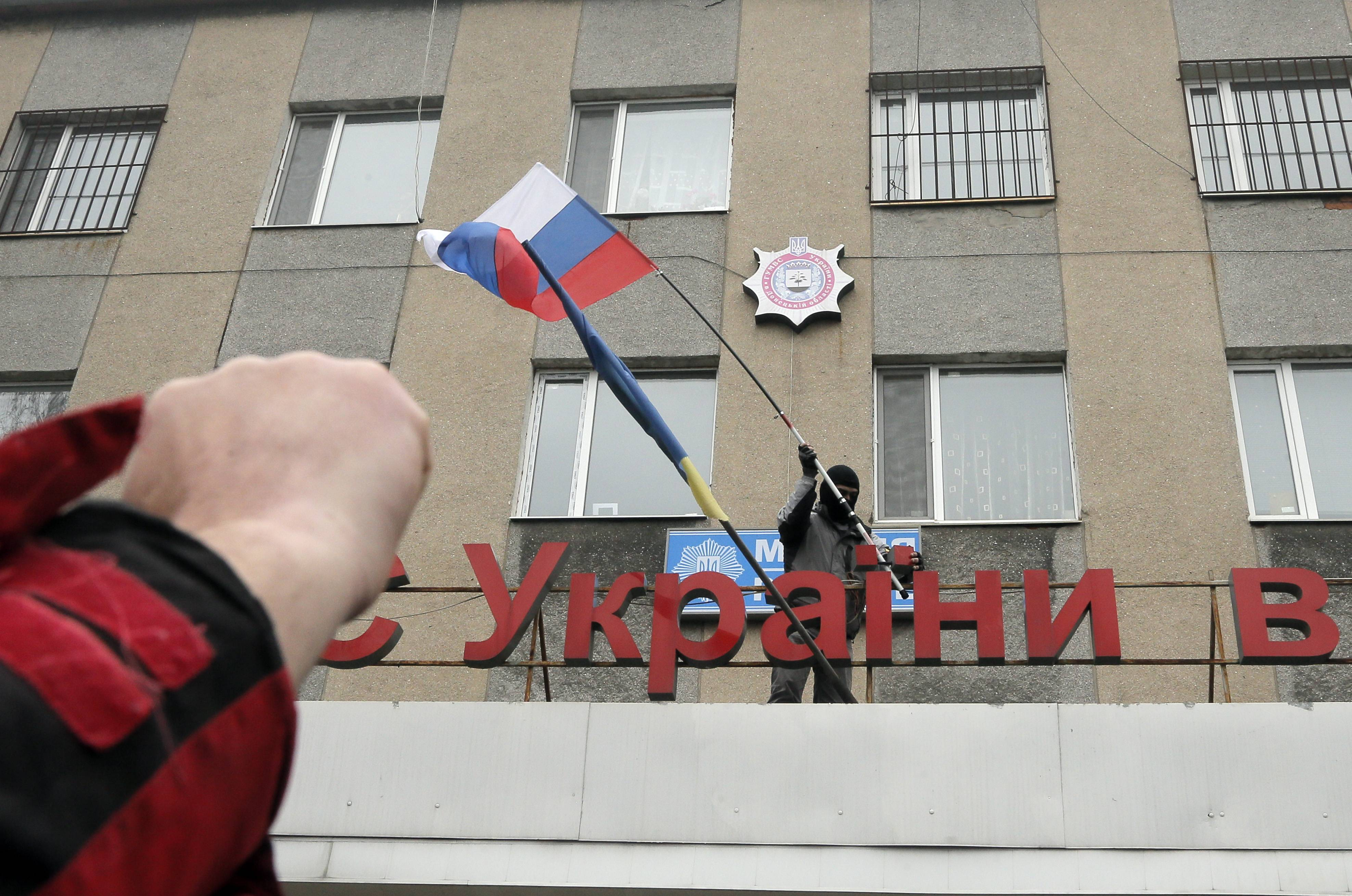A pro-Russian man places a Russian flag over a police station Monday during a mass storming in the eastern Ukrainian town of Horlivka. Several government buildings has fallen to mobs of Moscow loyalists in recent days as unrest spreads across the east of the country.