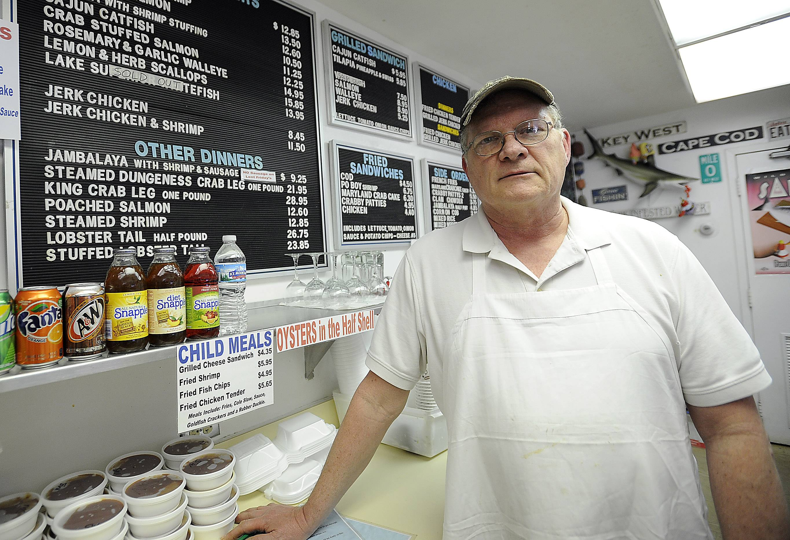 Andy Johnson, owner of Don's Dock in Des Plaines, stands next to his menu sign showing that Lake Superior whitefish is sold out. Whitefish is a traditional Passover food, but it's been difficult to find in stock because of fishermen's difficulty with the rough winter.