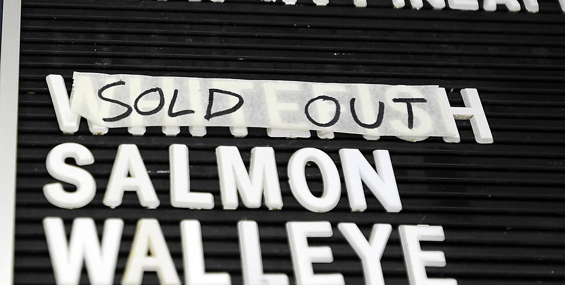 Andy Johnson has taped over his whitefish menu sign selection showing that Lake Superior whitefish is sold out.