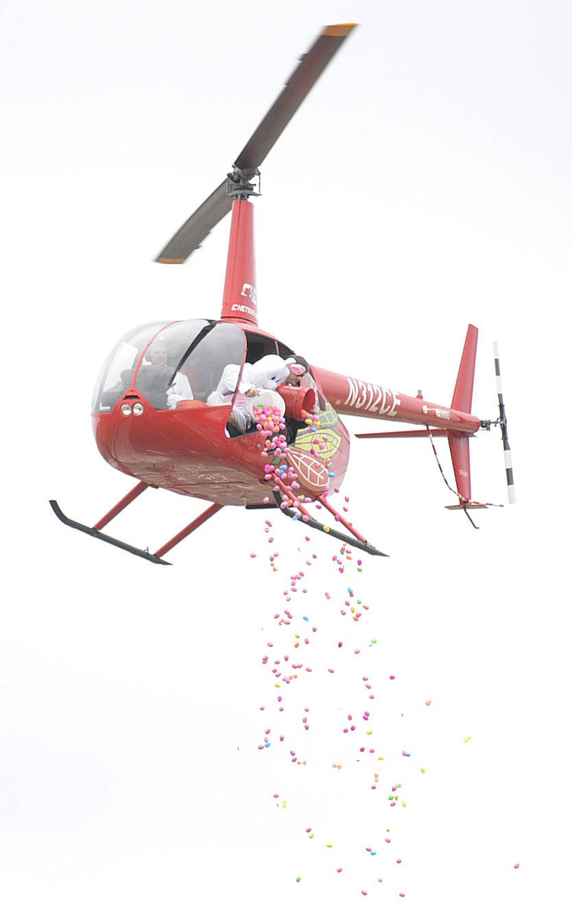 The Easter Bunny and Chris Meegan, of Chicago Helicopter Express, dump seven 5-gallon buckets of candy-filled plastic eggs, adding to thousands already placed in a grassy field, at the the start of the first ever helicopter egg drop at Faith Baptist Mill Creek Church in Geneva on Saturday. Over 12,000 eggs were available at the hunt, which drew about 800 families to the event.