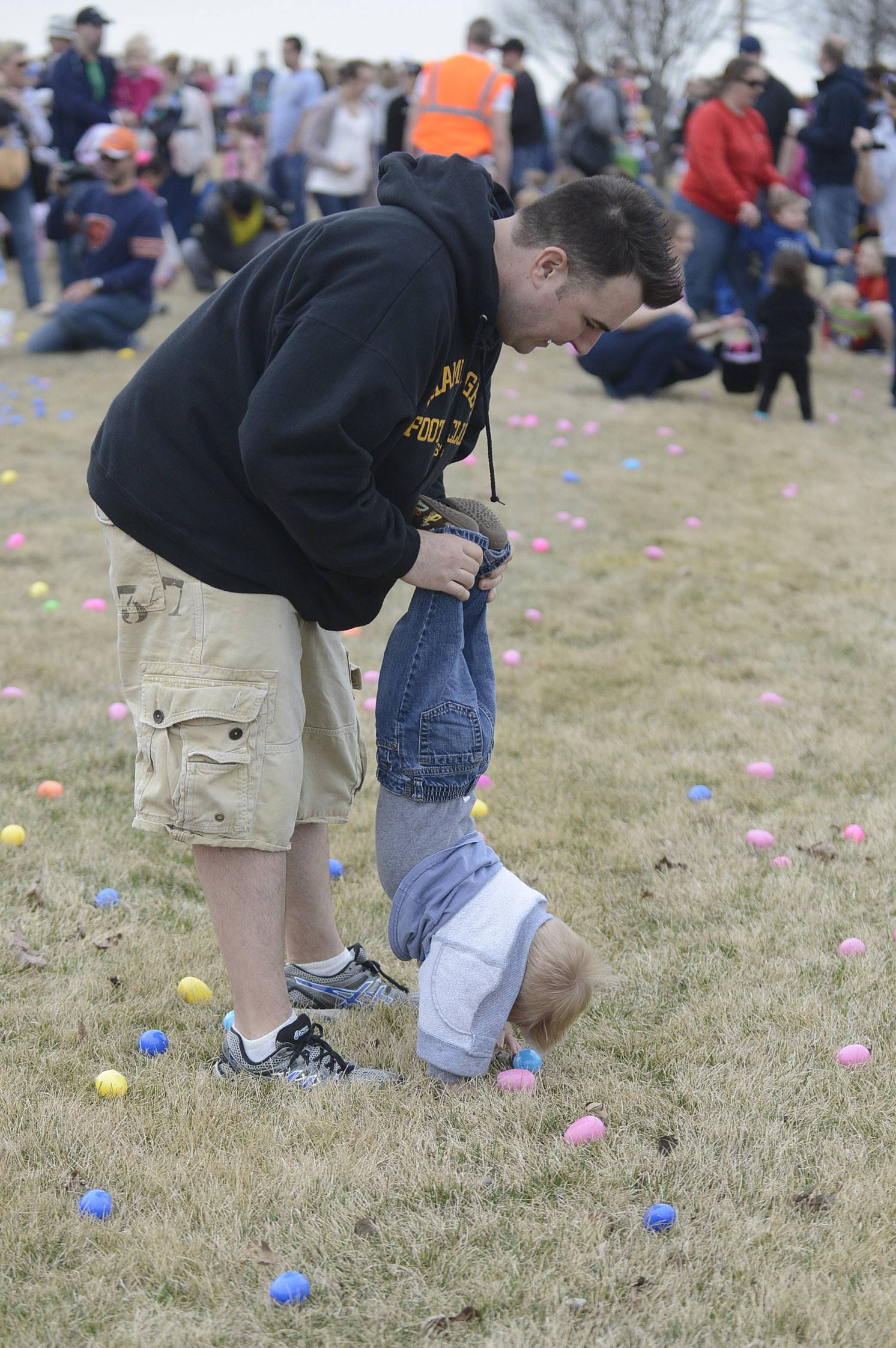 Eddie English, of Geneva, and his son, Deacon, 13 months, use a different technique to collect a few eggs at Faith Baptist Mill Creek Creek Church's egg hunt in Geneva on Saturday.